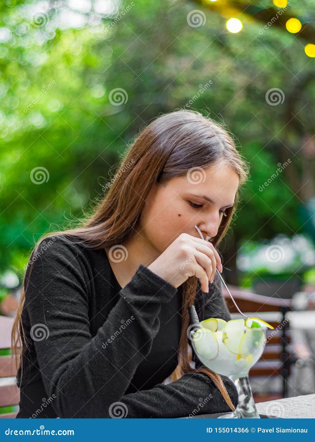 Fille de brune d adolescent avec de longs cheveux mangeant la crème glacée en café extérieur