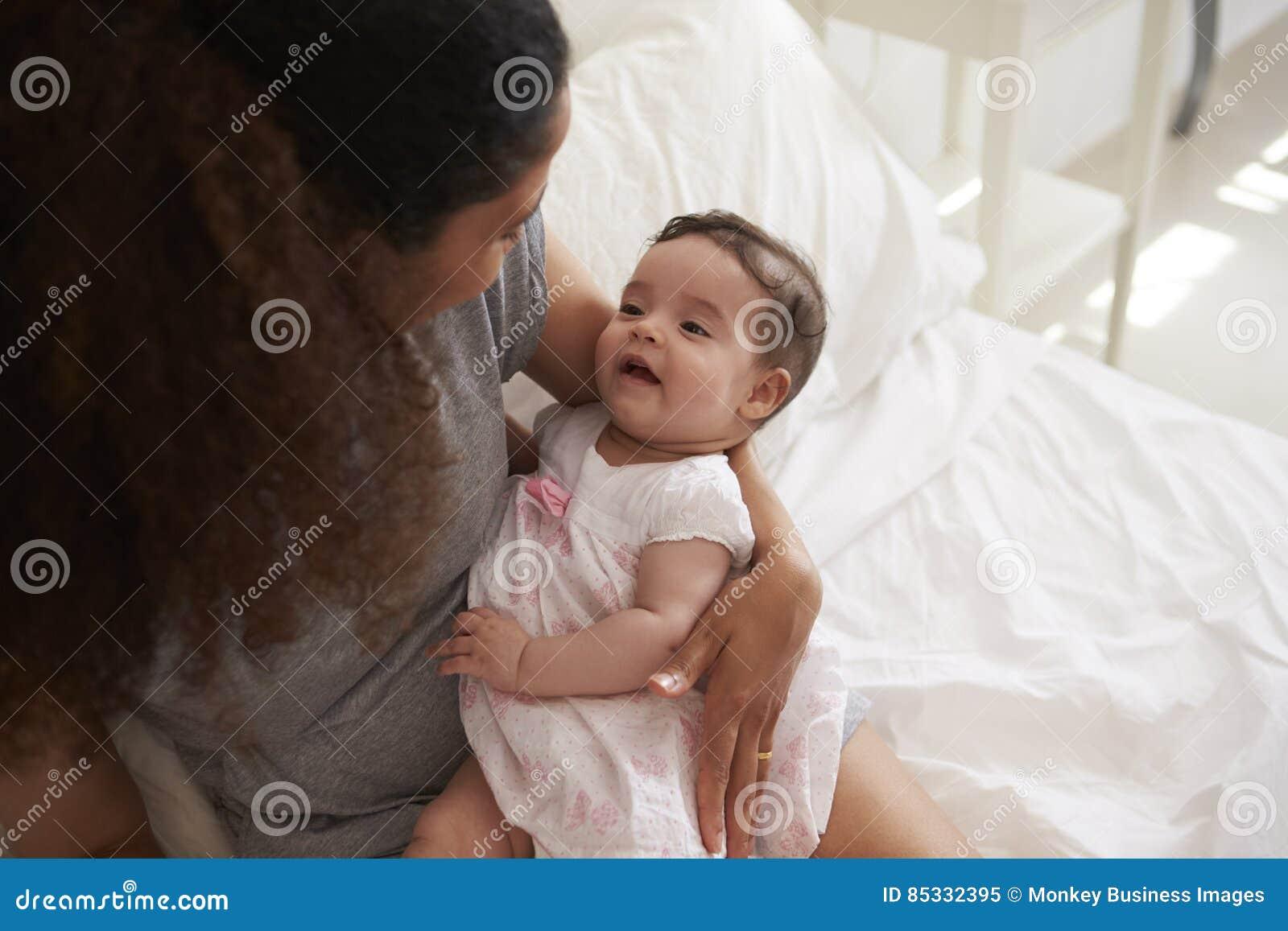 Fille de caresse de bébé de mère dans la chambre à coucher à la maison