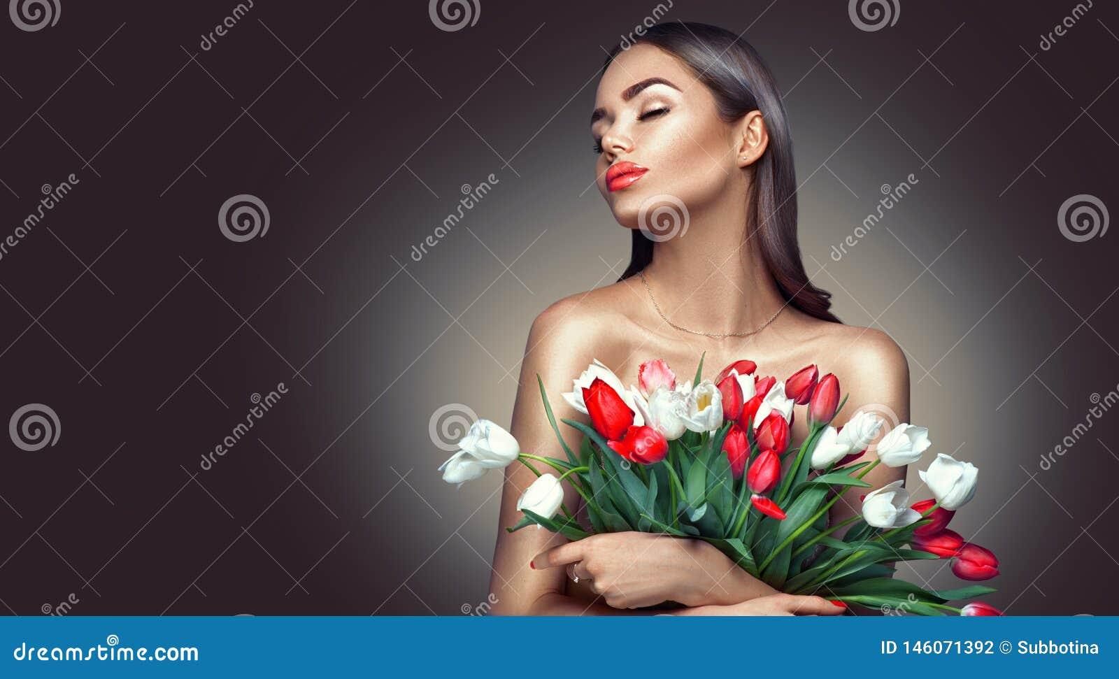 Fille de charme de beaut? avec des fleurs de tulipe de ressort Belle jeune femme avec un groupe de fleurs color?es de tulipe