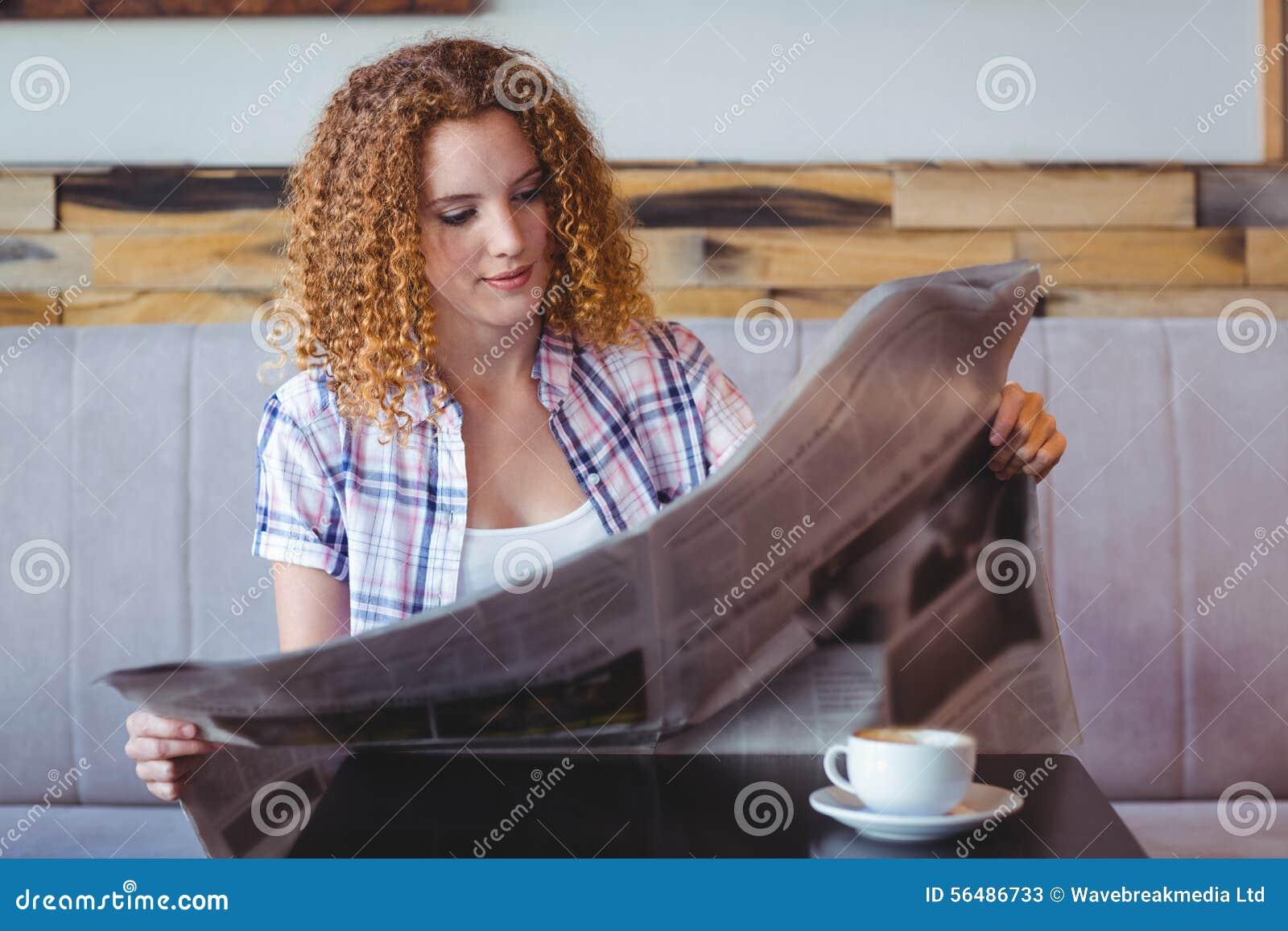 Fille de cheveux assez bouclés ayant la tasse de café et lisant le journal