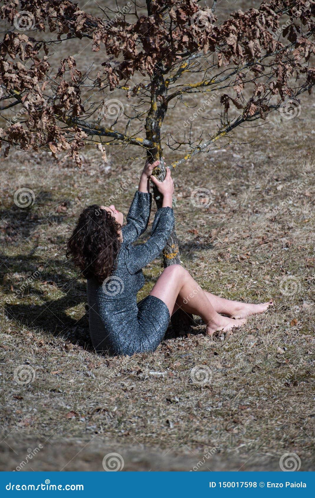 Fille de cheveux onduleux de brune dans les montagnes, jouant la séance sur l herbe secouant un jeune arbre