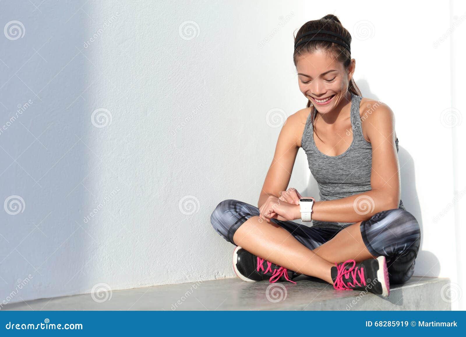 Fille de forme physique employant le smartwatch de traqueur d activité en tant que moniteur de fréquence cardiaque pour la séance