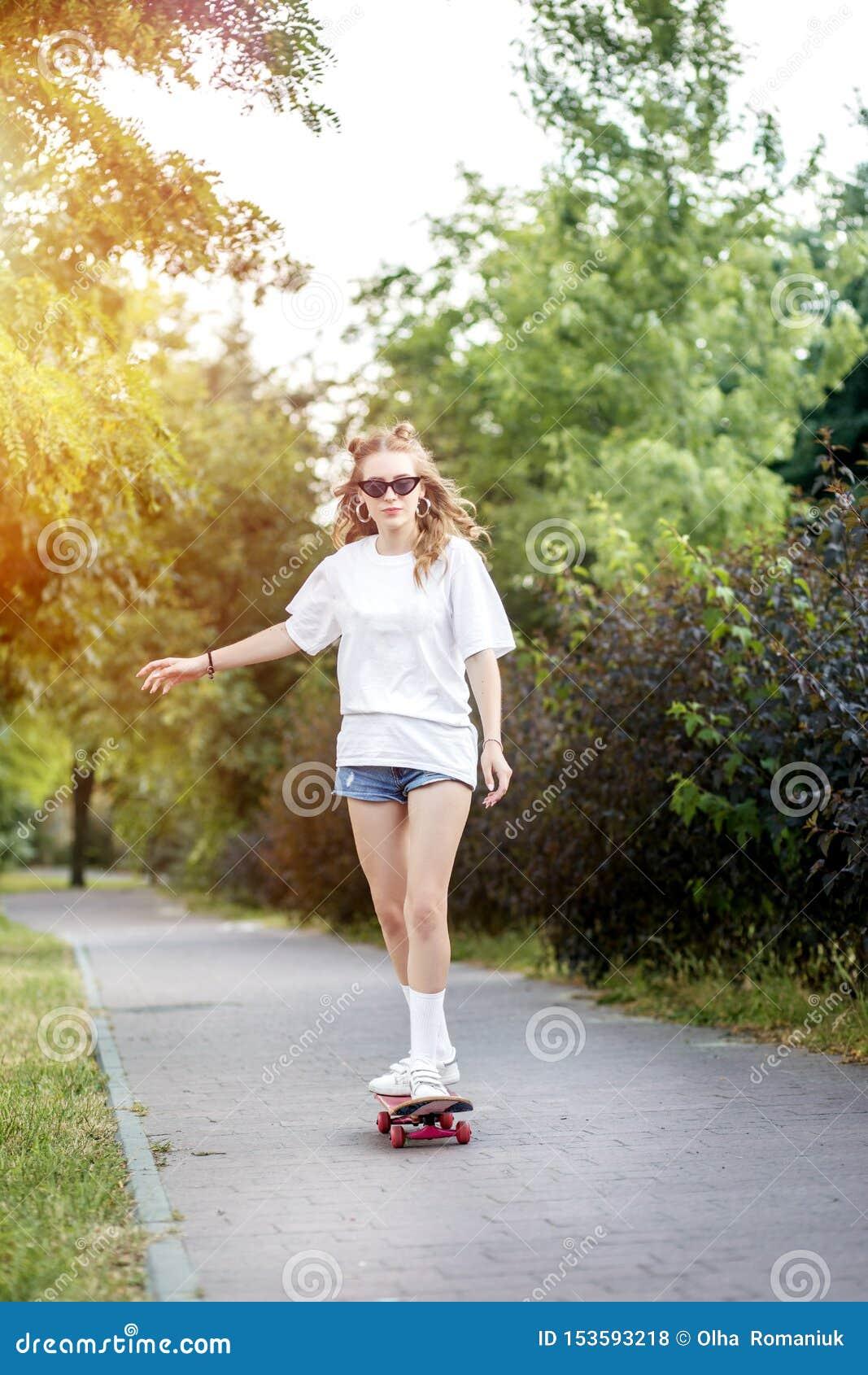 Fille de jeune adolescent montant un panneau de patin en parc Le concept du mode de vie, loisirs