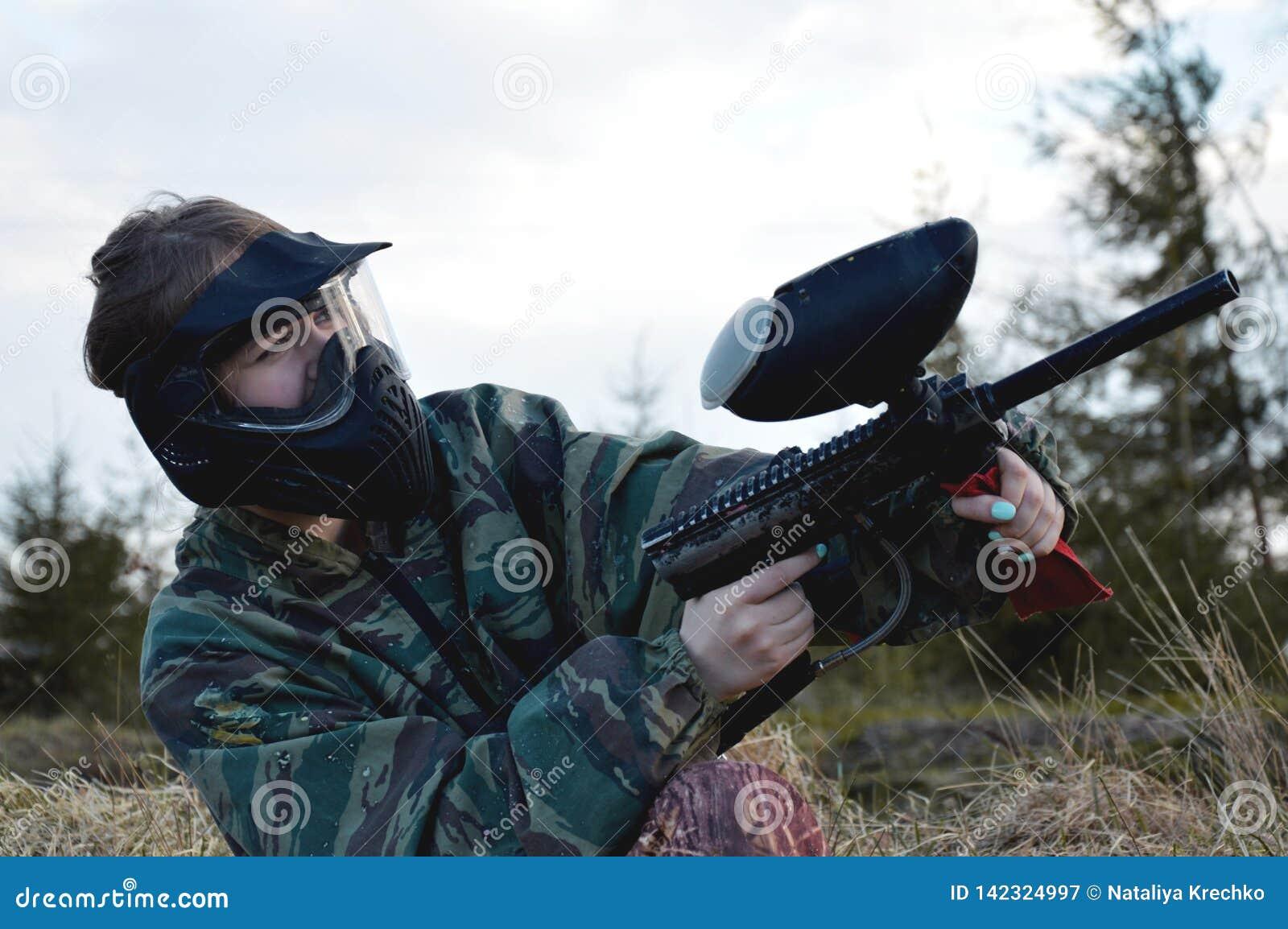 Fille de joueur de sport de Paintball dans l uniforme et le masque protecteurs de camouflage