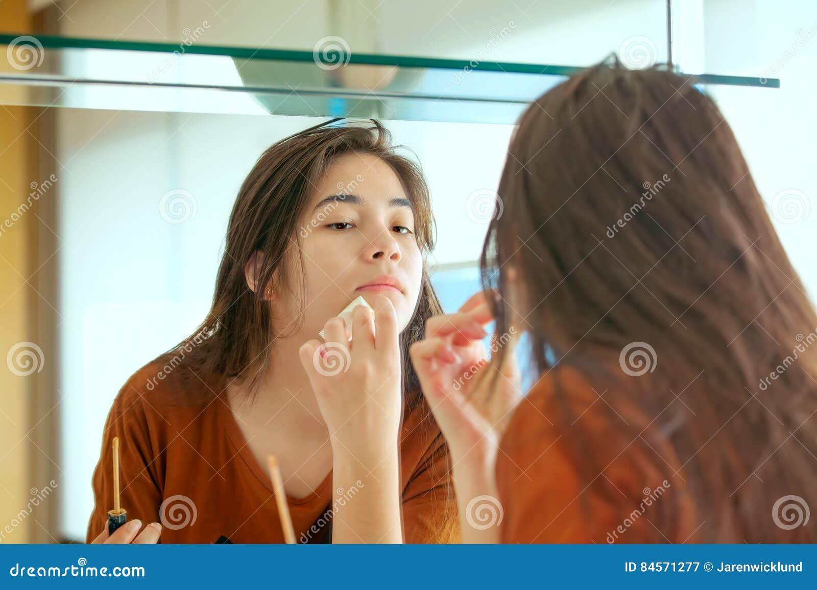 Fille de l adolescence Biracial mettant le maquillage dessus dans le miroir