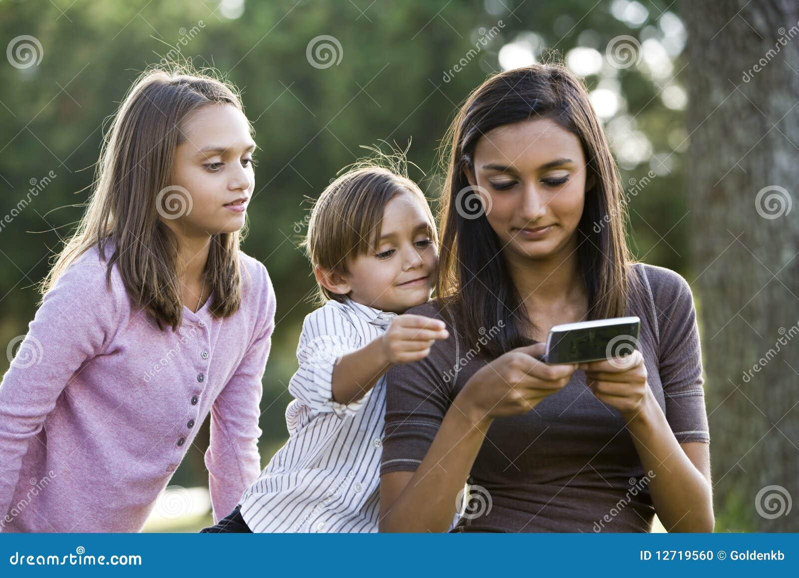 Fille de l adolescence texting, une plus jeune montre d enfants de mêmes parents