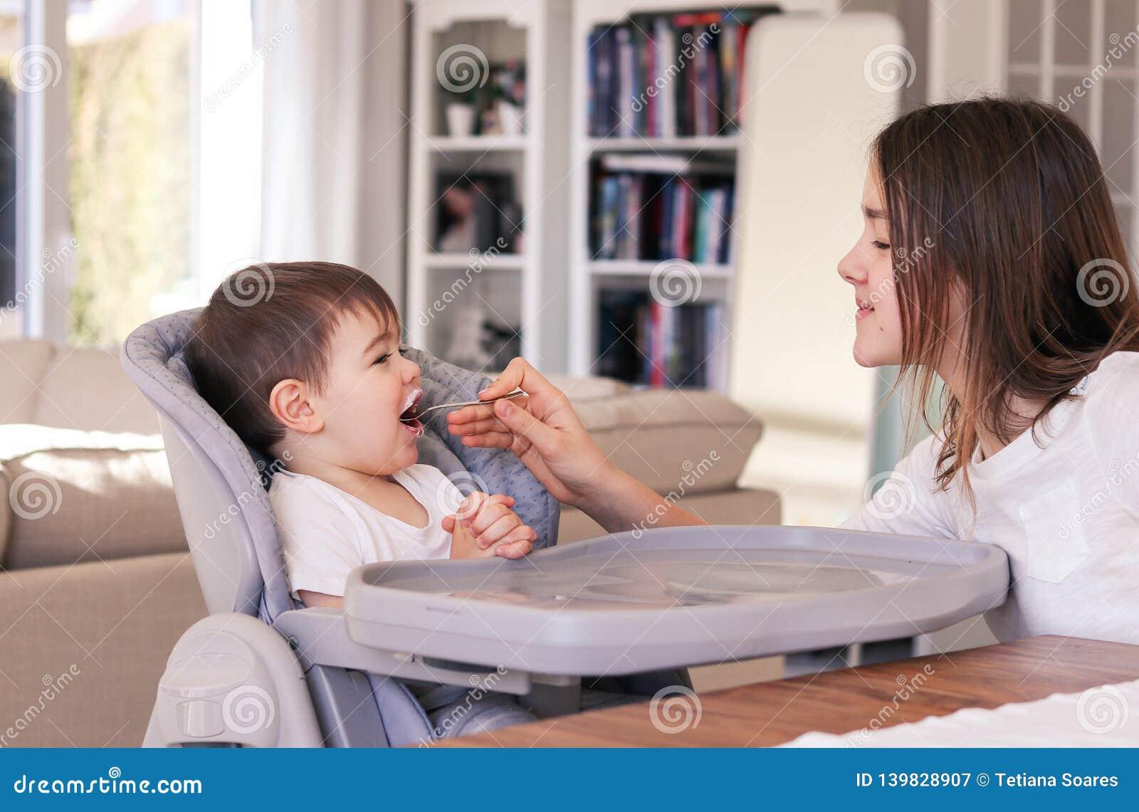 Fille de la préadolescence de soin alimentant son petit frère s asseyant dans la chaise d alimentation de taille à la maison Les
