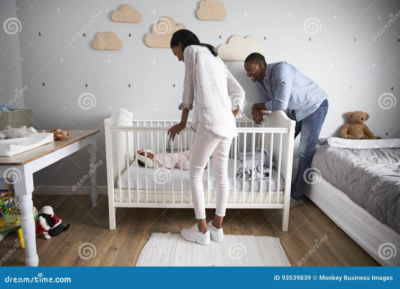 Fille de Looking At Baby de mère et de père dans le berceau de crèche