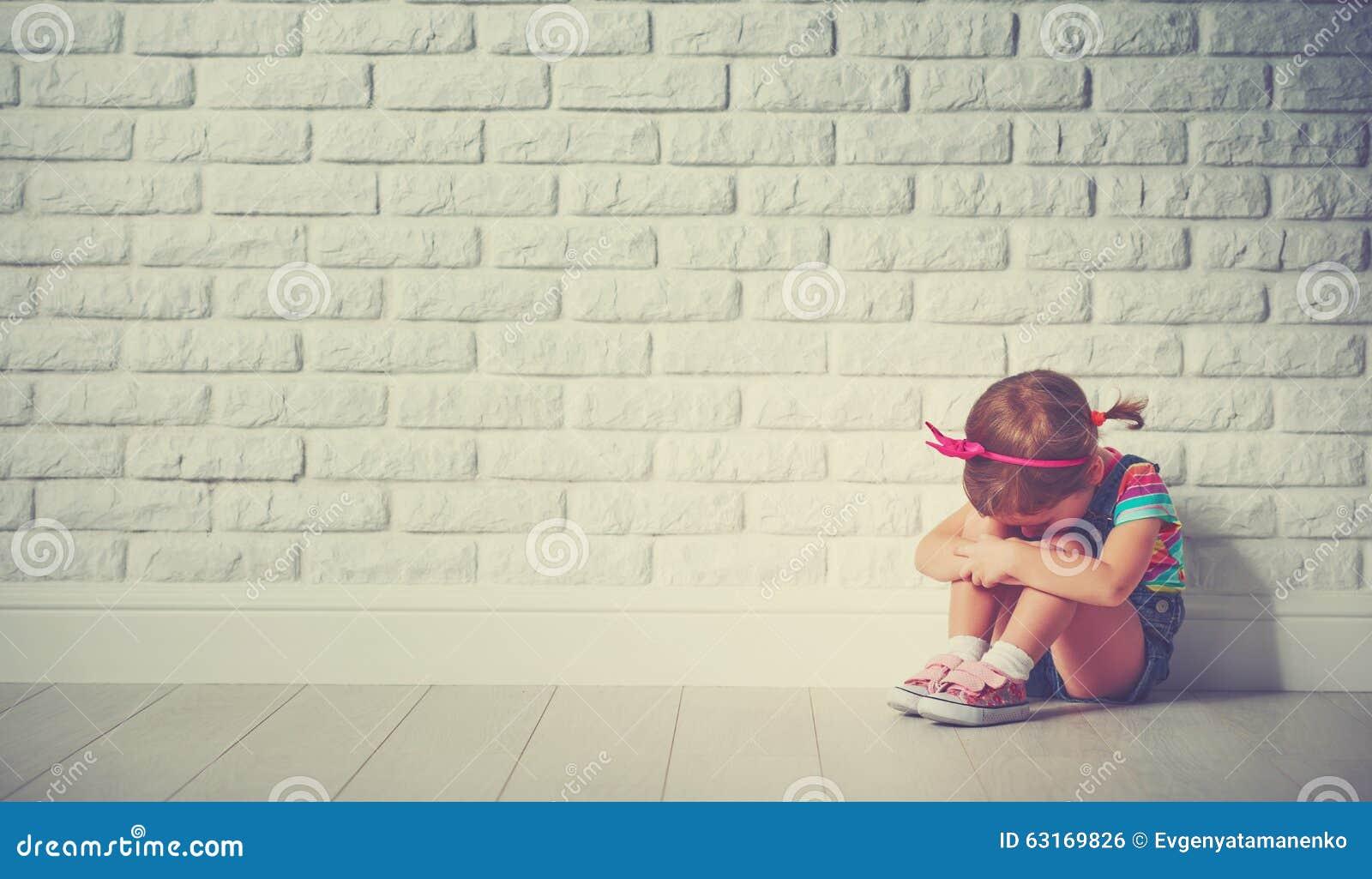 Fille de petit enfant pleurant et triste au sujet du mur de briques