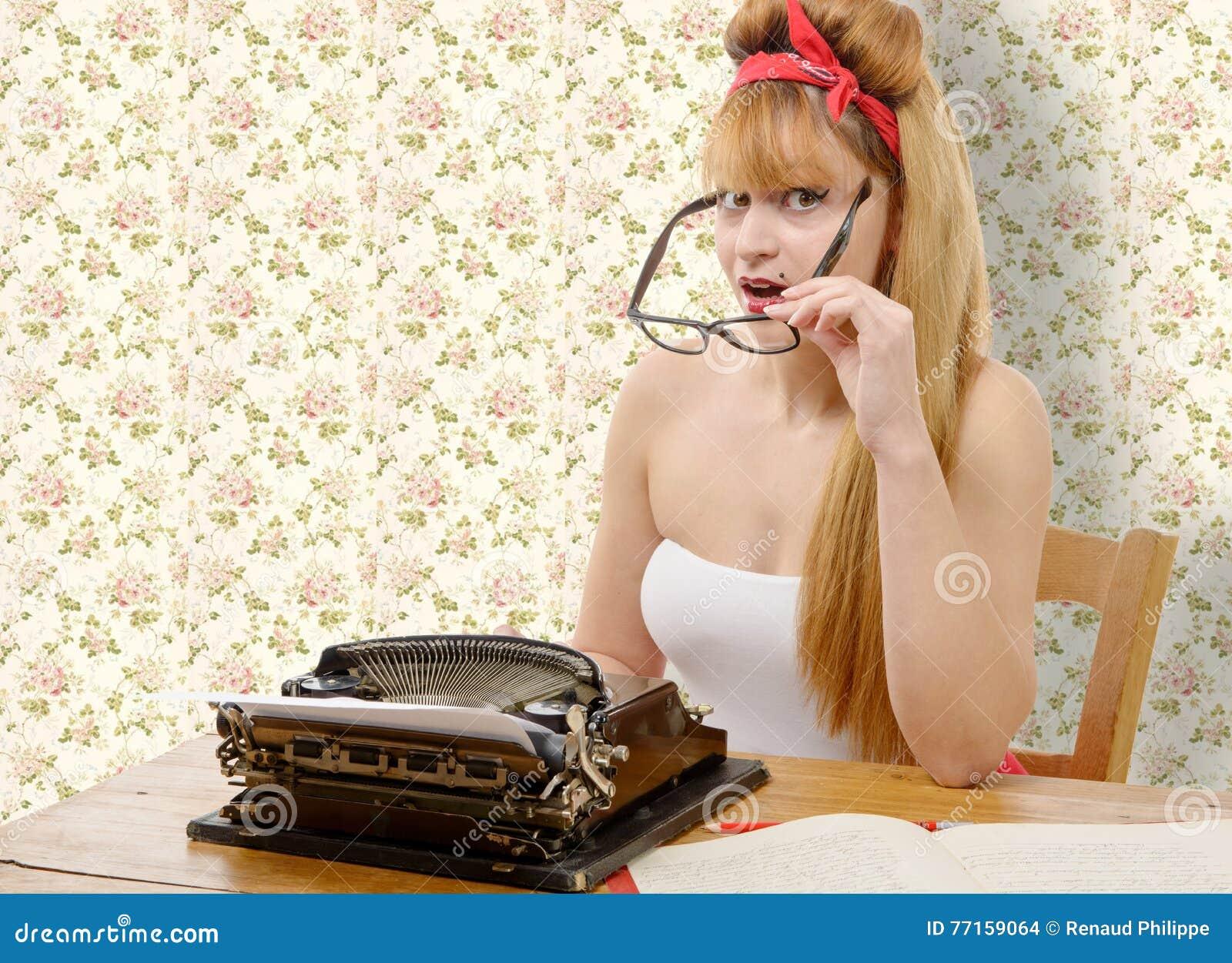 Fille de pin-up avec la vieille machine à écrire