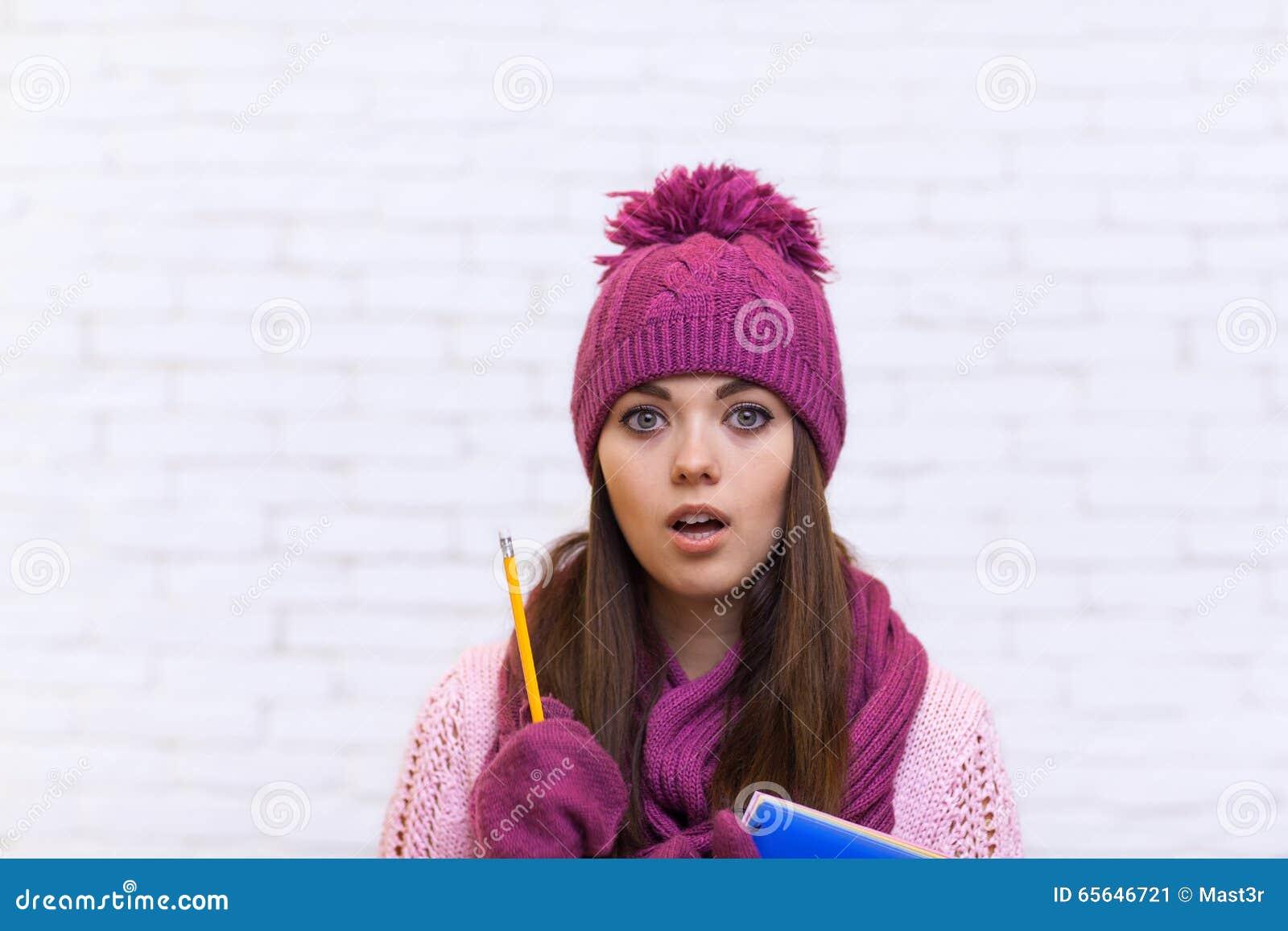 Fille de Pondering Worried Attractive d étudiant dans le chapeau rose tenant le crayon de dossier