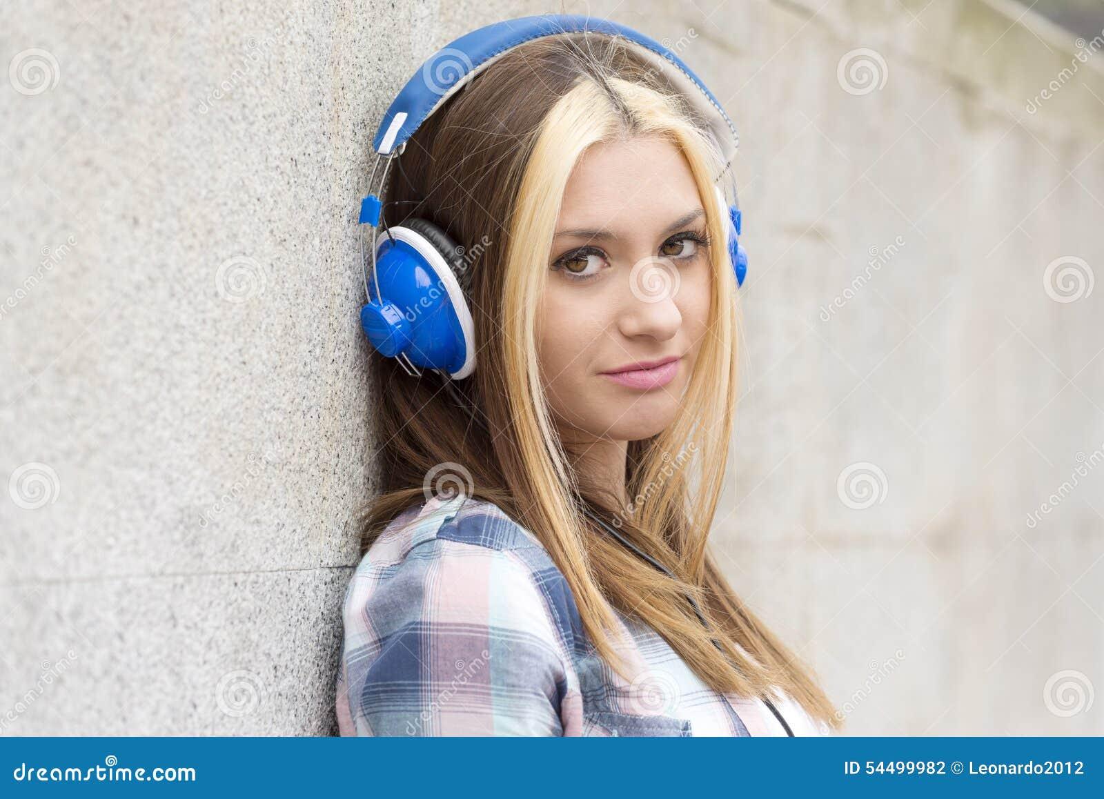 Fille de portrait de plan rapproché la belle écoutent musique avec des écouteurs