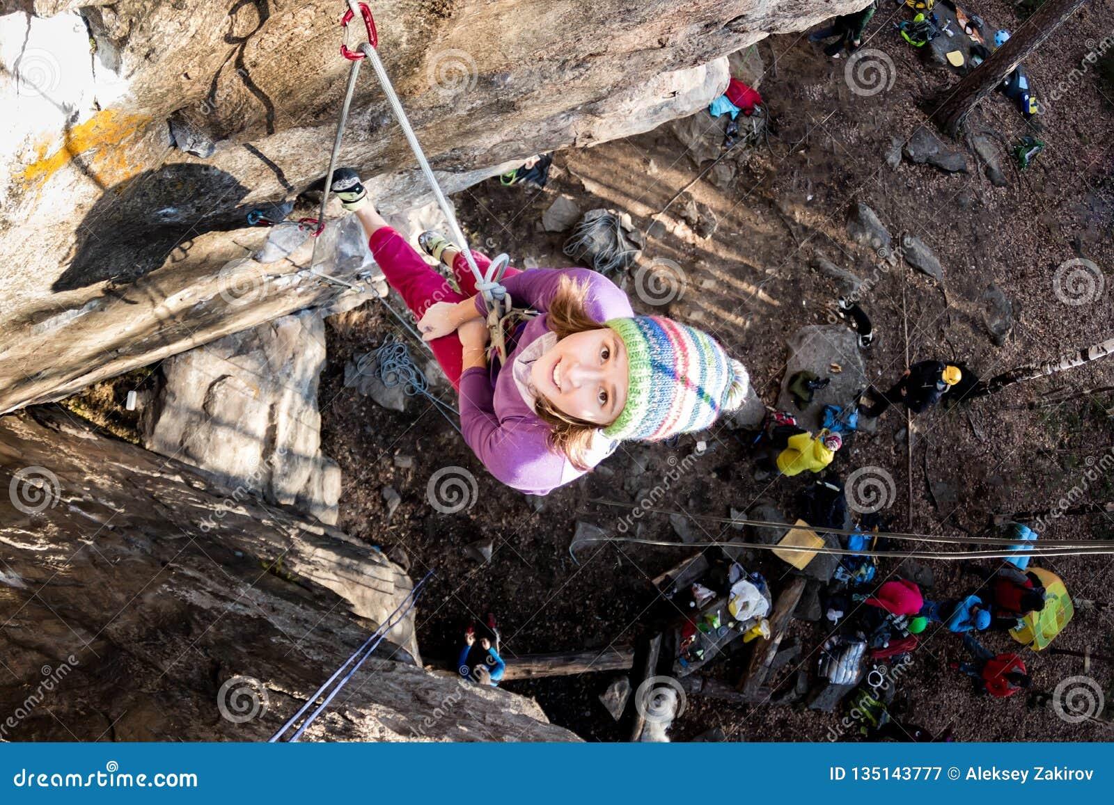 Fille de Roche-grimpeur pleurant en douleur accrochant sur une corde avec un visage triste en s élevant sur une roche