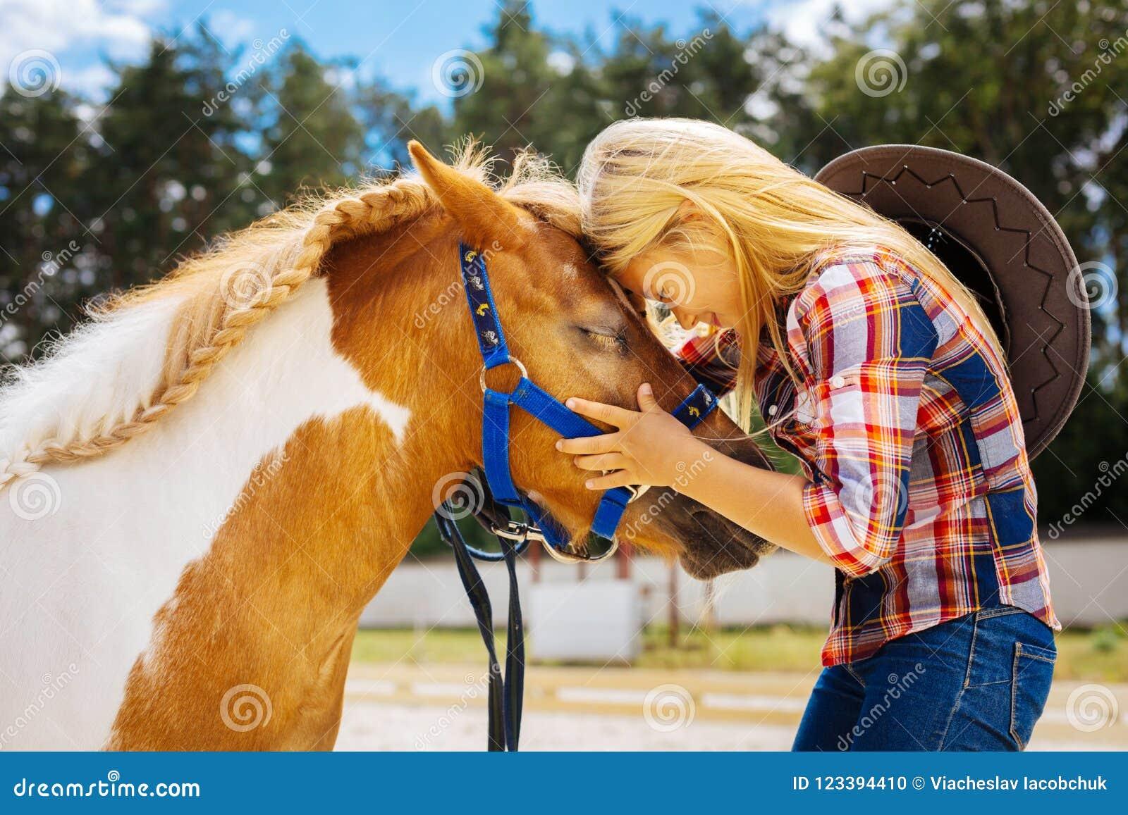 Fille de soin de cowboy se sentant émotive tout en voyant son poney mignon