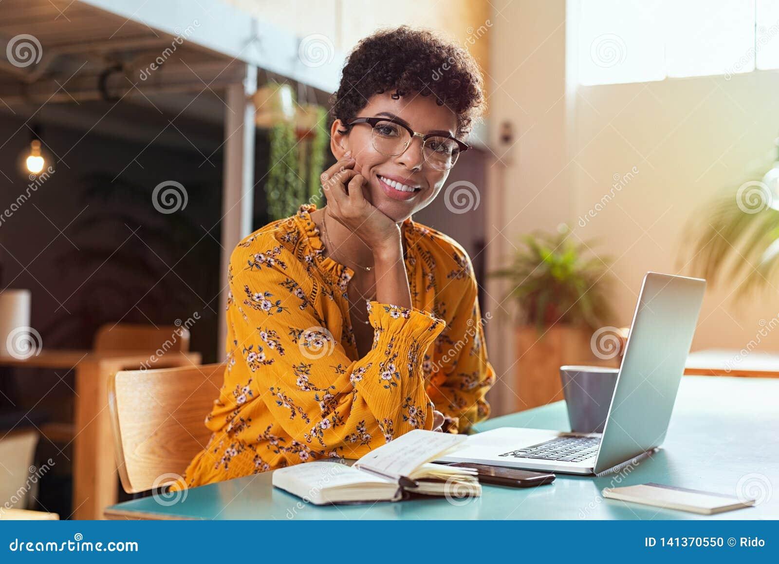 Fille de sourire à l aide de l ordinateur portatif