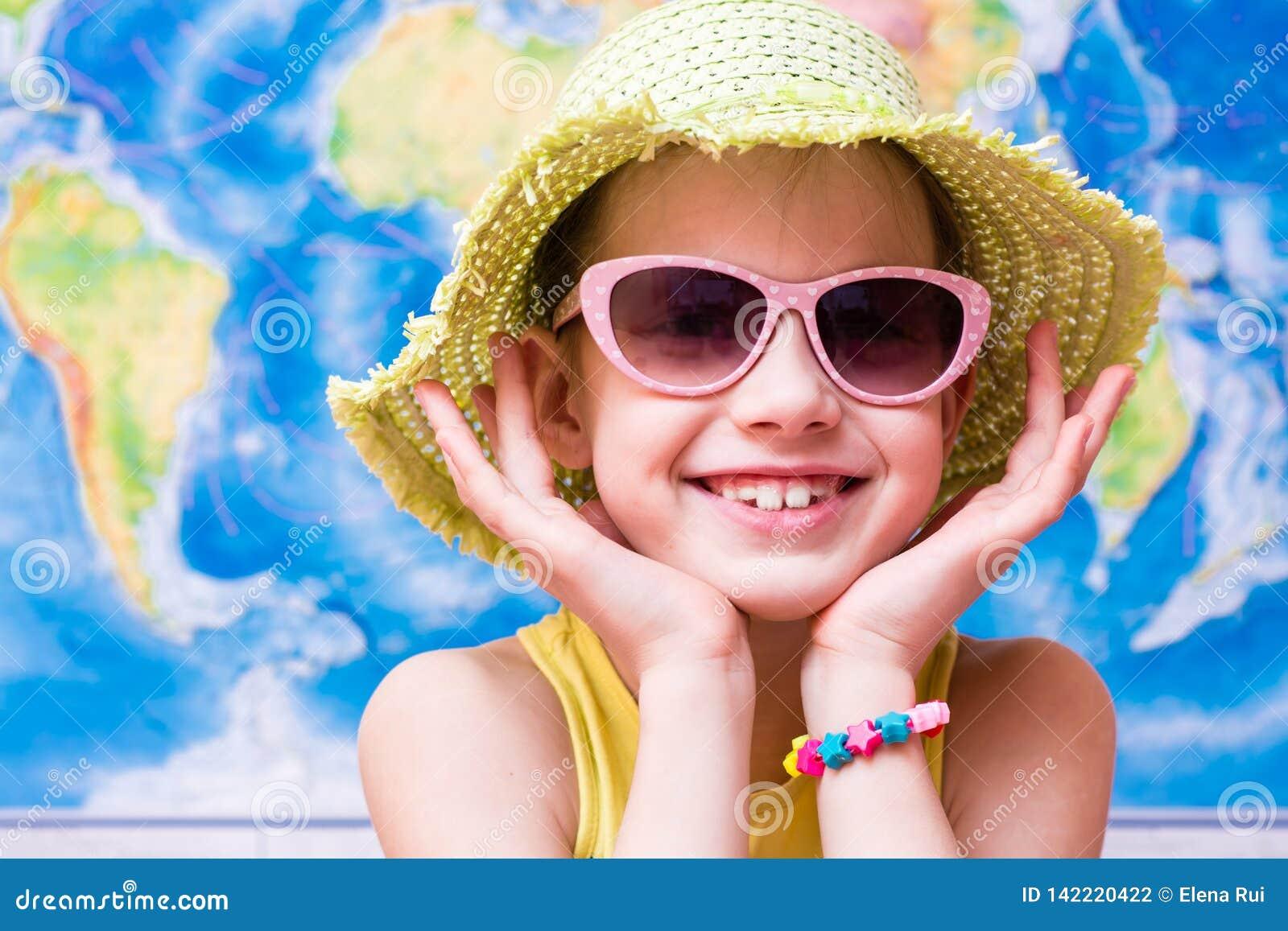 Fille de sourire dans un chapeau et des lunettes de soleil sur le fond de la carte du monde