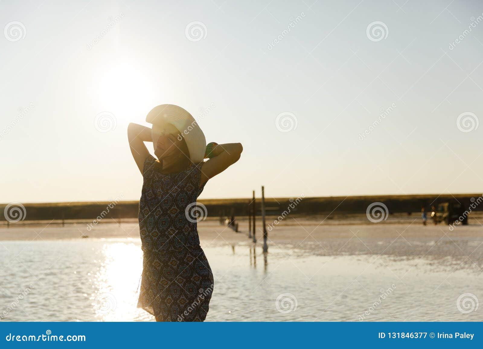 Fille de sourire heureuse dans le chapeau blanc appréciant le soleil, étendue de lac de sel de Bascunchak