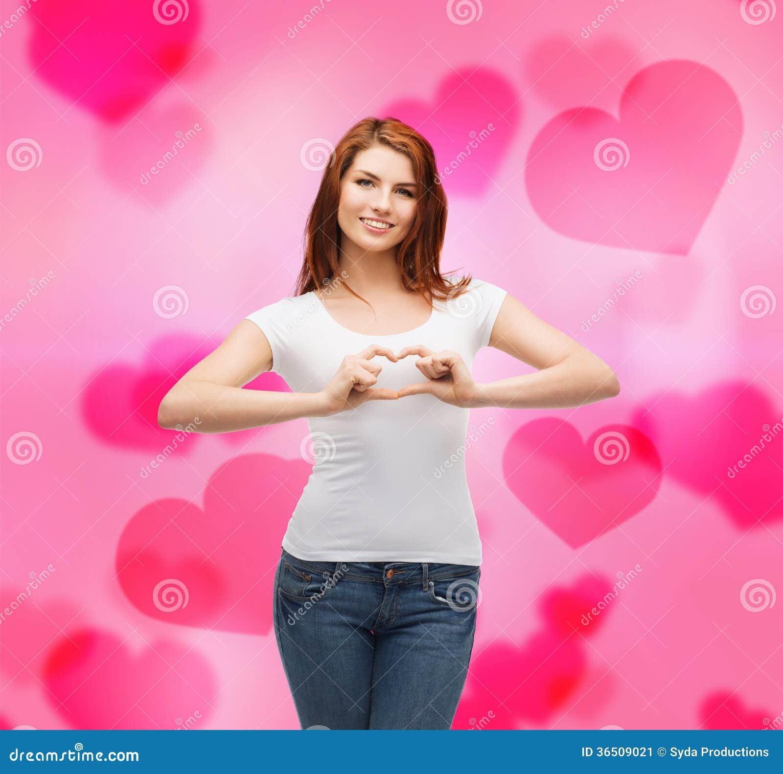 Fille de sourire montrant le coeur avec des mains