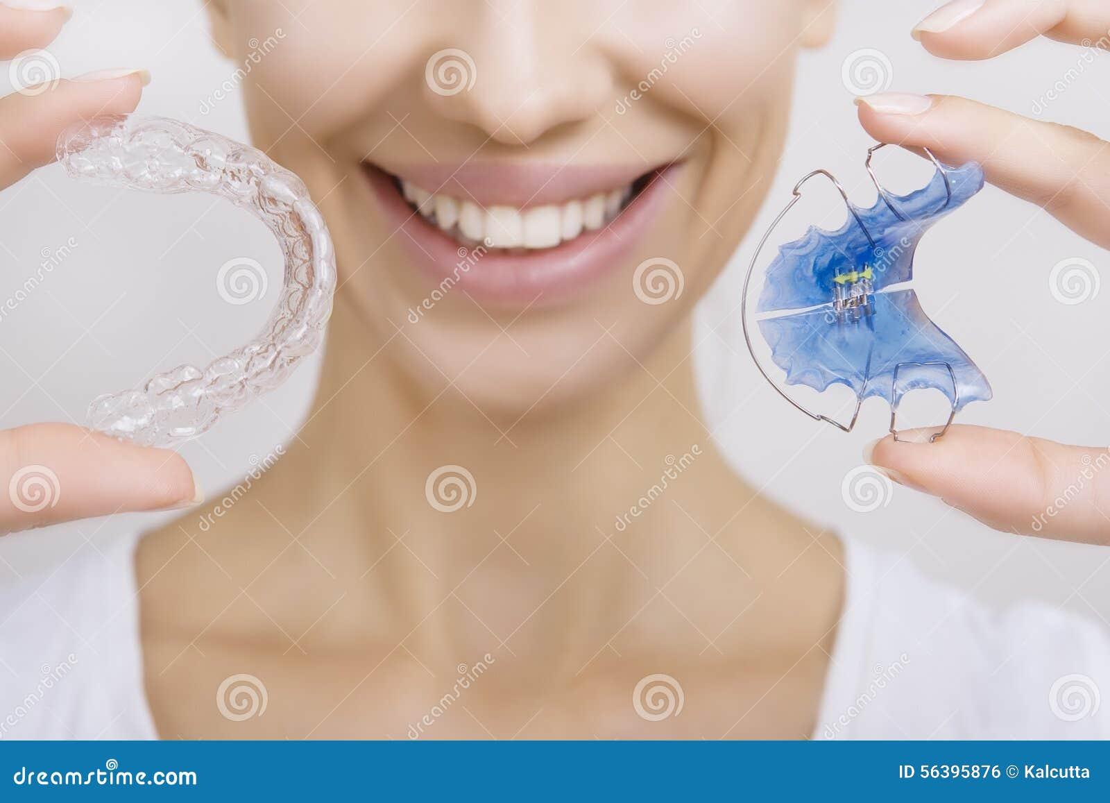 Fille de sourire tenant l arrêtoir pour les dents et le plateau de dent
