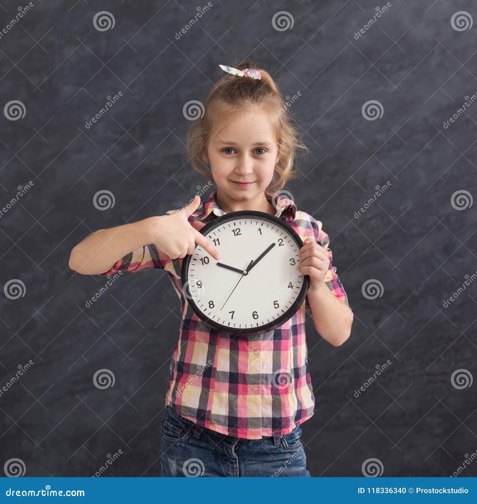 Fille de sourire tenant la grande horloge, se dirigeant là-dessus