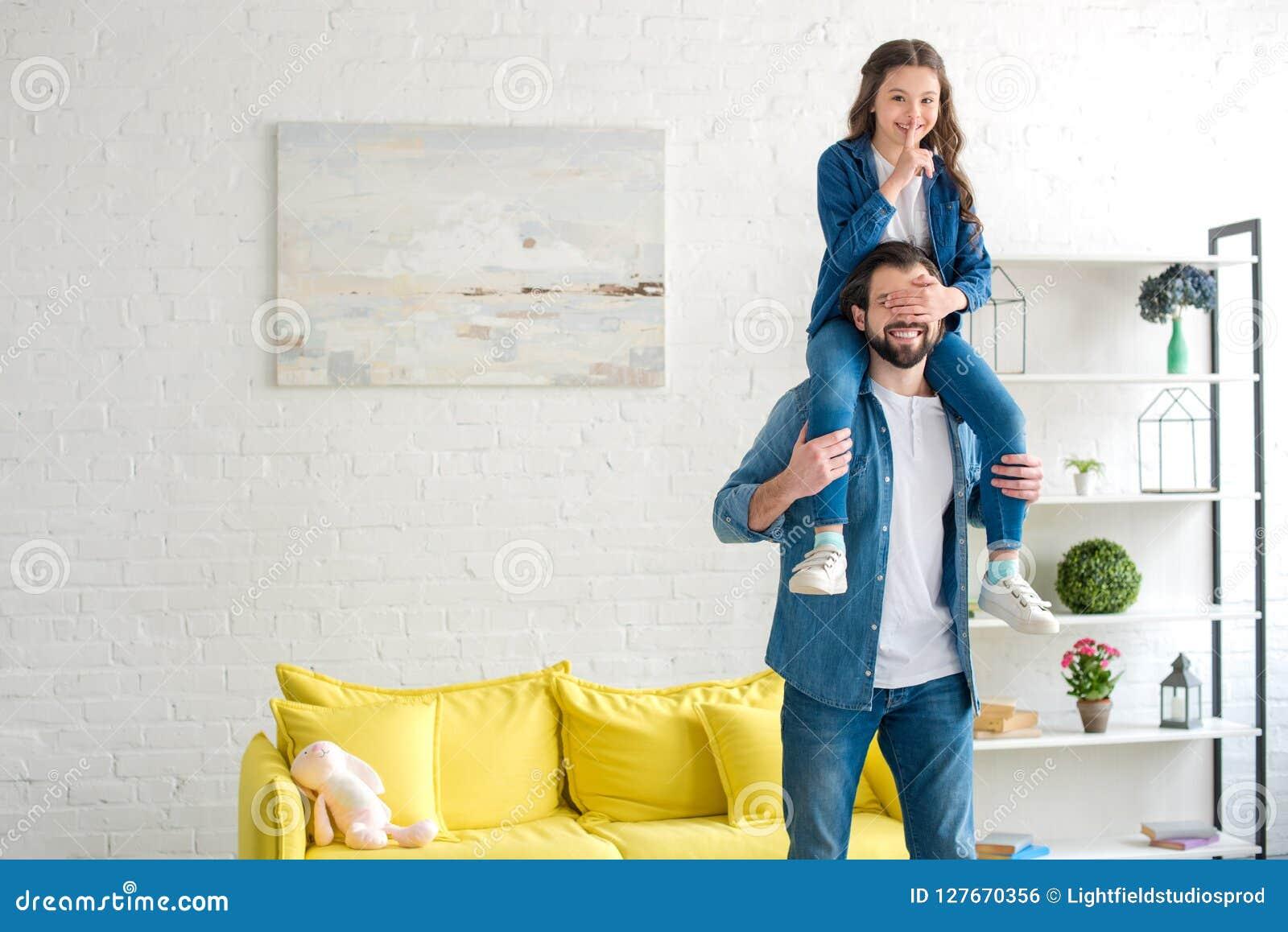 Fille de sourire de transport de père heureux sur le cou et l amusement de avoir ensemble à la maison