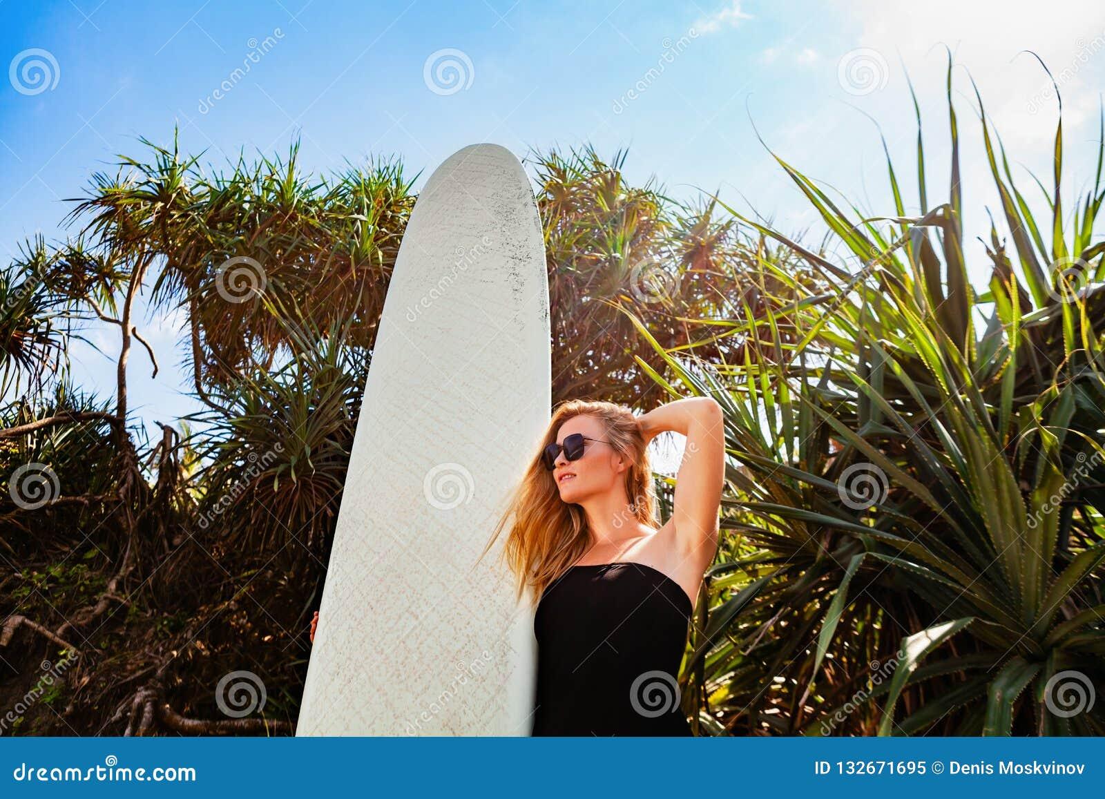 Fille de surfer sur la plage tropicale