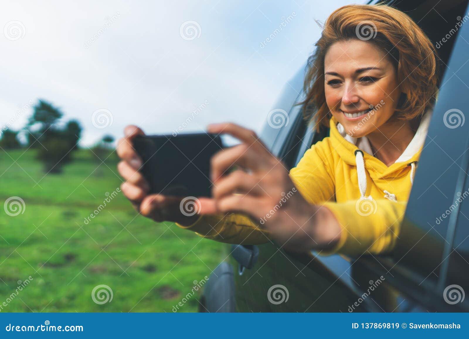 Fille de touristes de sourire dans une fenêtre ouverte d une voiture automatique prenant le selfie de photo au téléphone intellig