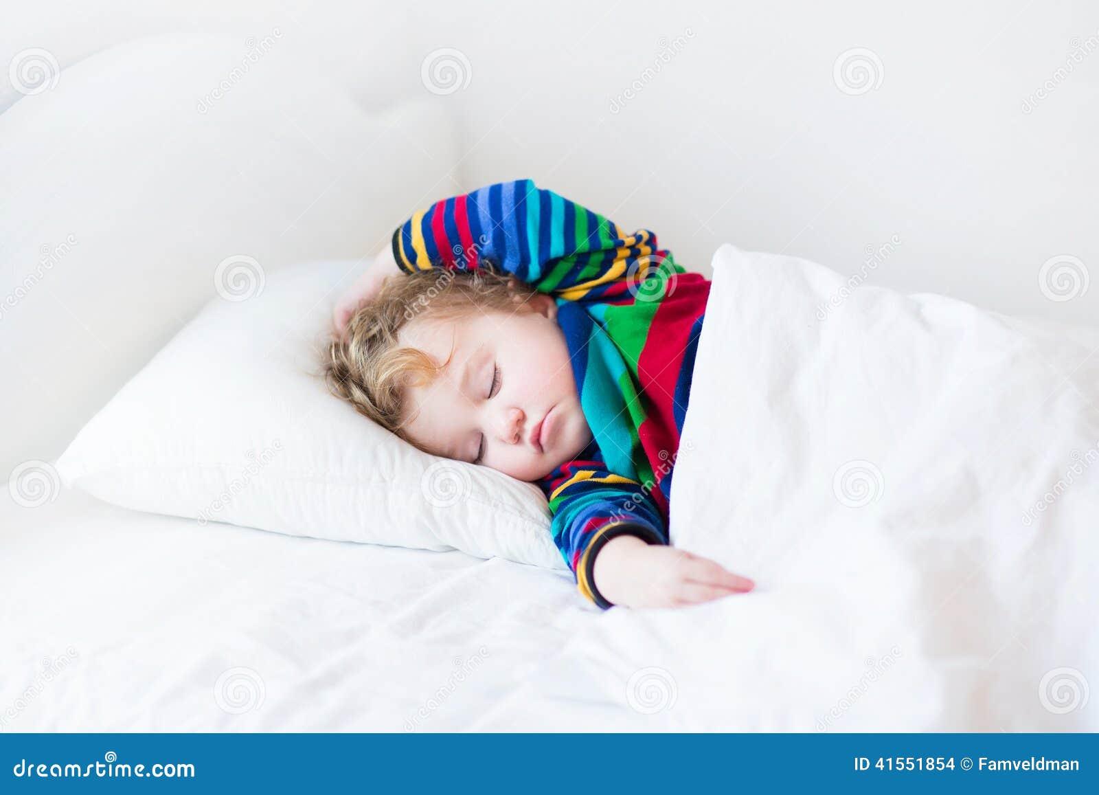 Fille drôle d enfant en bas âge dormant dans un lit blanc