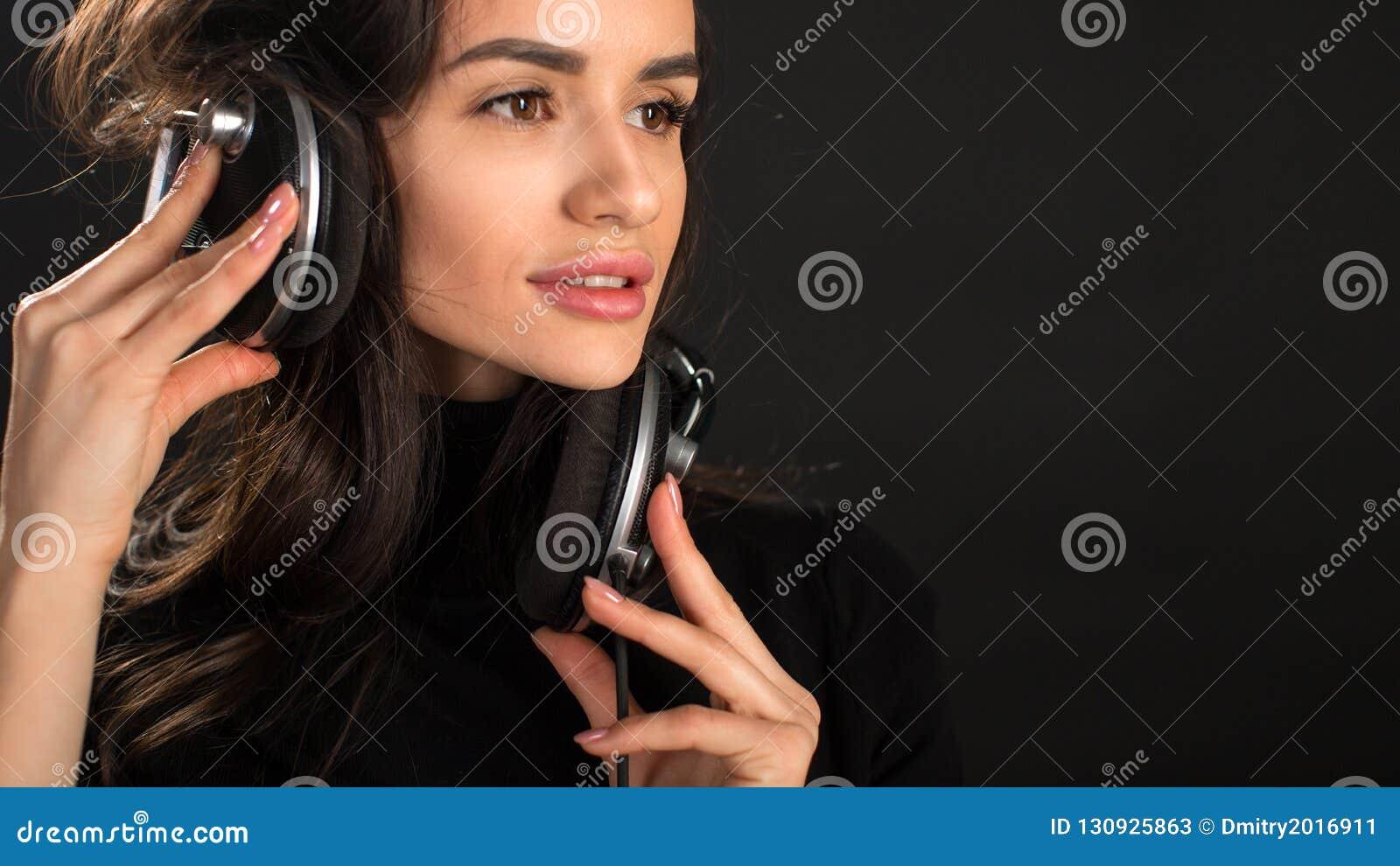 Fille du DJ dans des battements de écoute de disco d écouteurs posant dans le studio au-dessus du fond foncé Jeune modèle caucasi