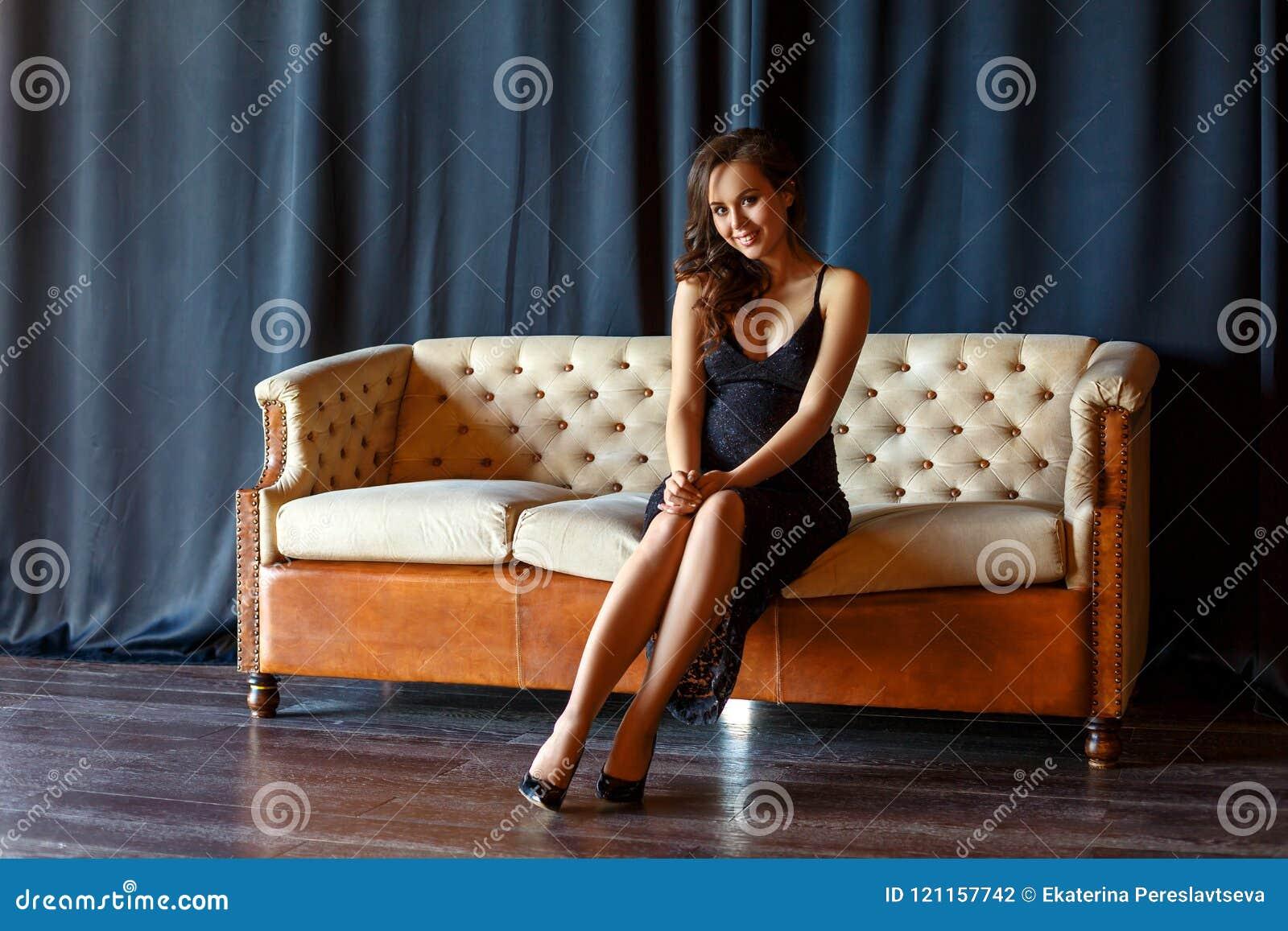 Fille enceinte s asseyant sur le divan dans une belle robe