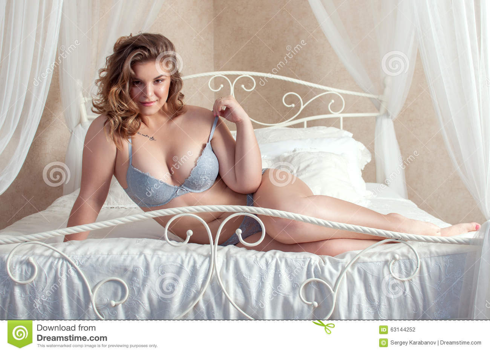 fille espi gle de taille plus se situant dans le lit photo stock image du positif fille 63144252. Black Bedroom Furniture Sets. Home Design Ideas
