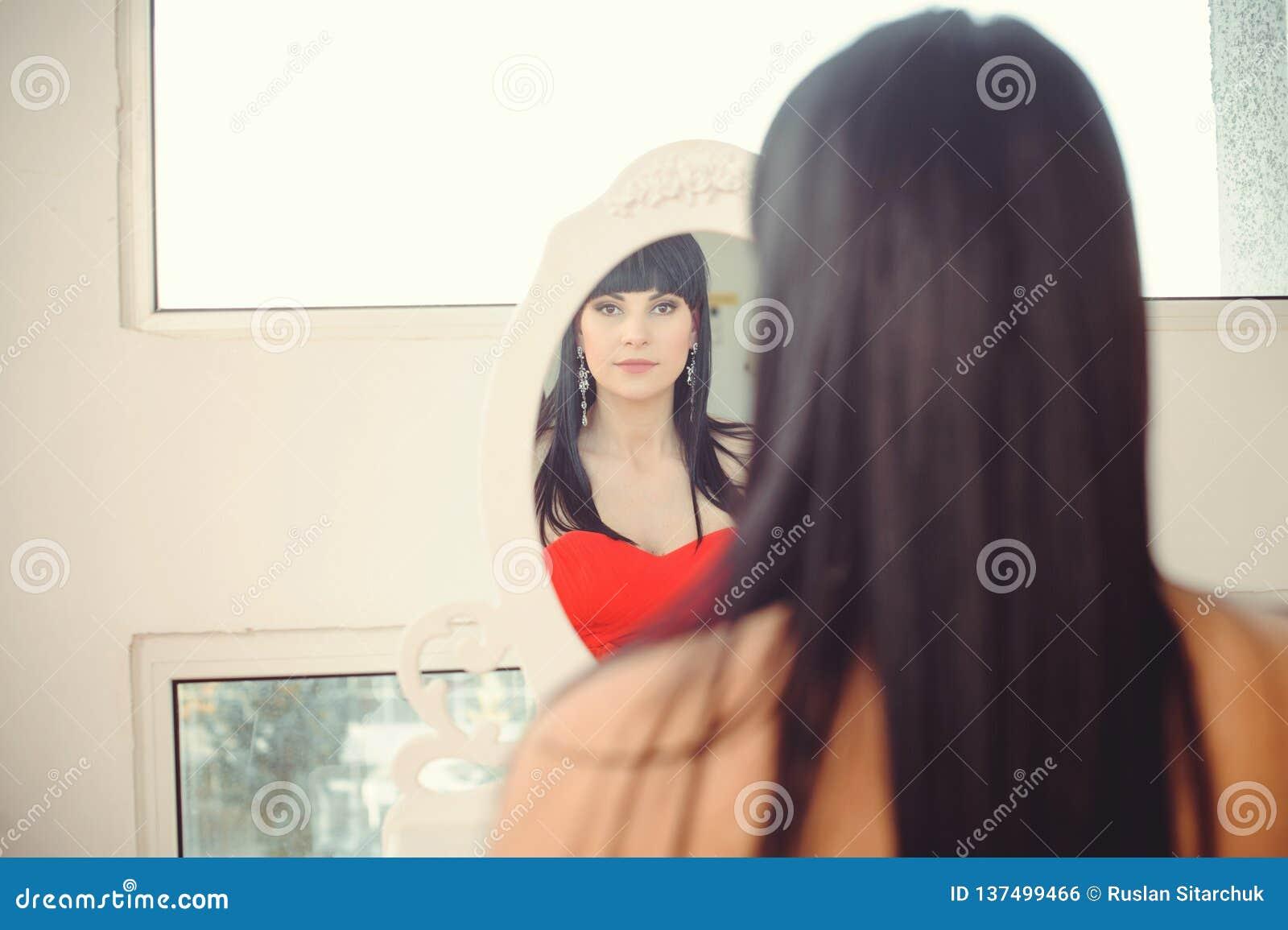 Fille essayant d habiller le regard dans le miroir, gai et heureux Bel Asiatique mignon de métis/jeune femme caucasienne en rouge