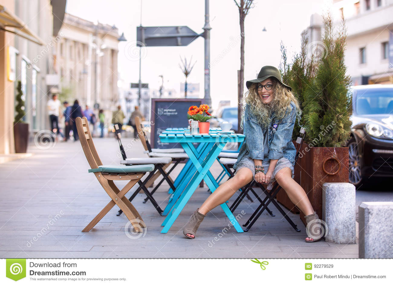 Fille folle à la table buvant une tasse de café dans la ville