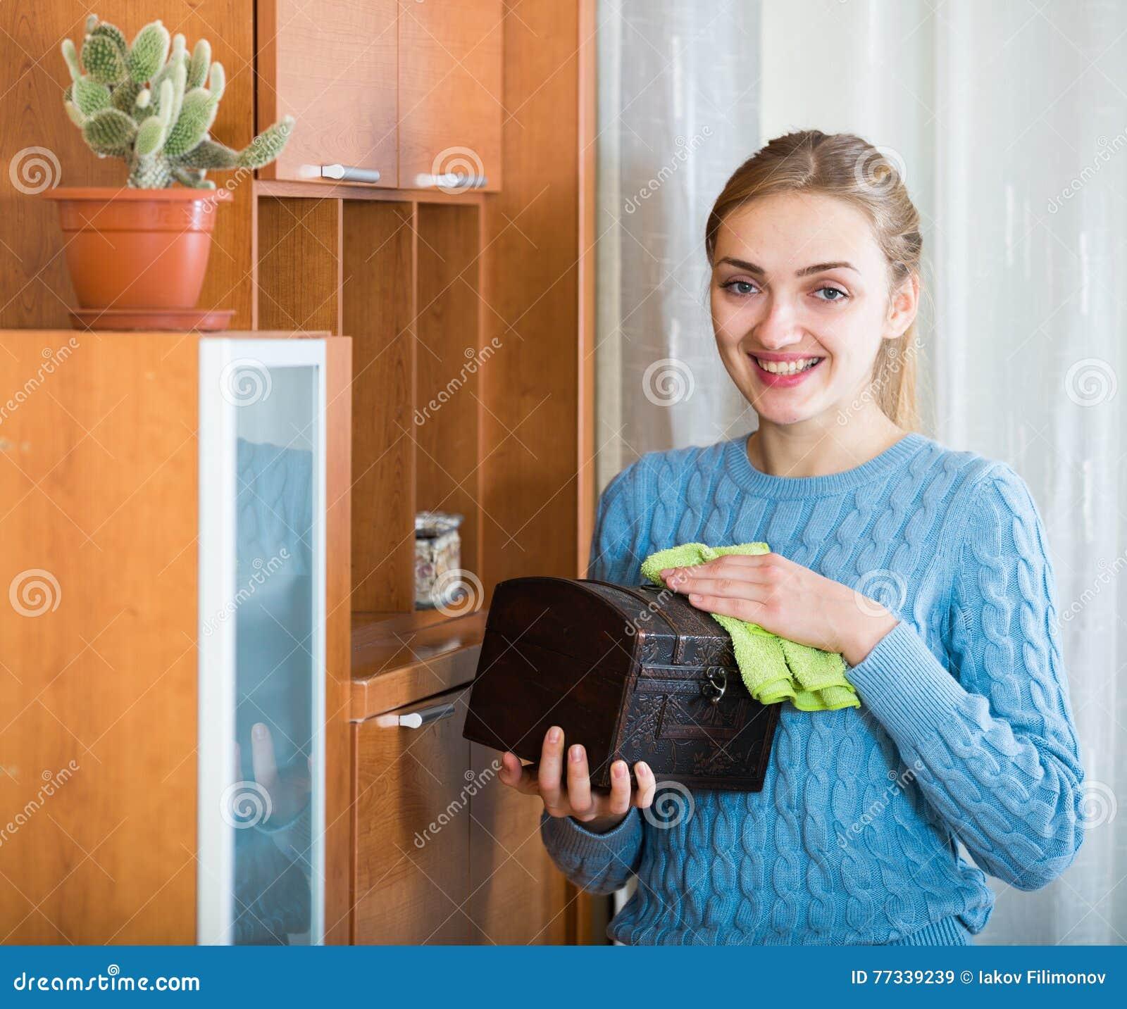 Fille gaie dans le débardeur bleu nettoyant à la maison