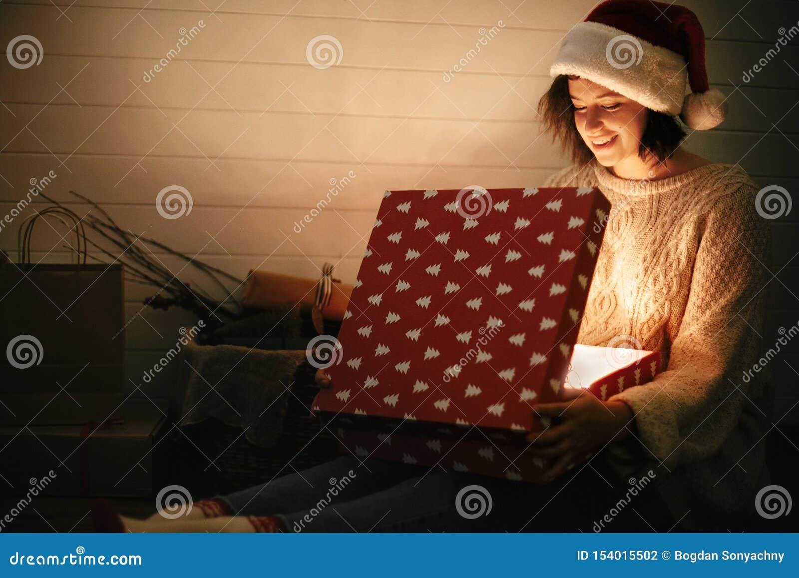 Fille heureuse élégante dans le chapeau de Santa et le boîte-cadeau s ouvrant de Noël de chandail confortable avec la lumière mag