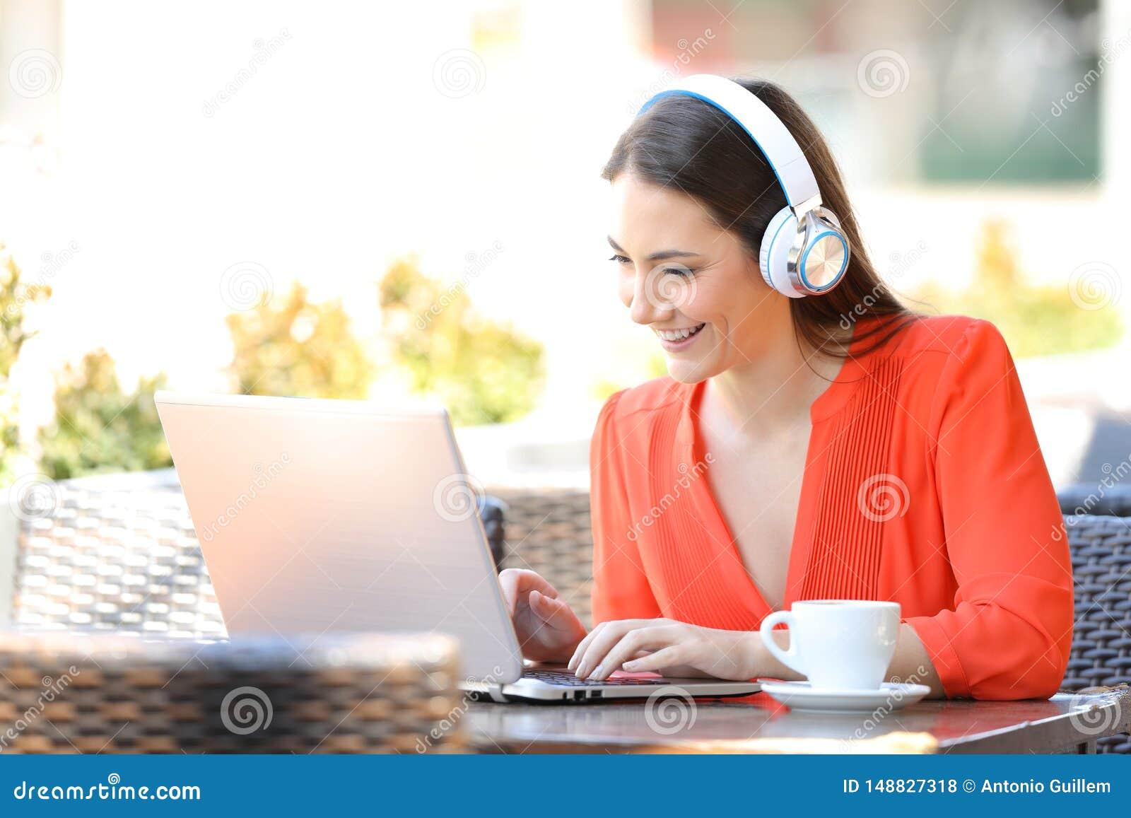 Fille heureuse avec des ?couteurs utilisant un ordinateur portable dans un caf?