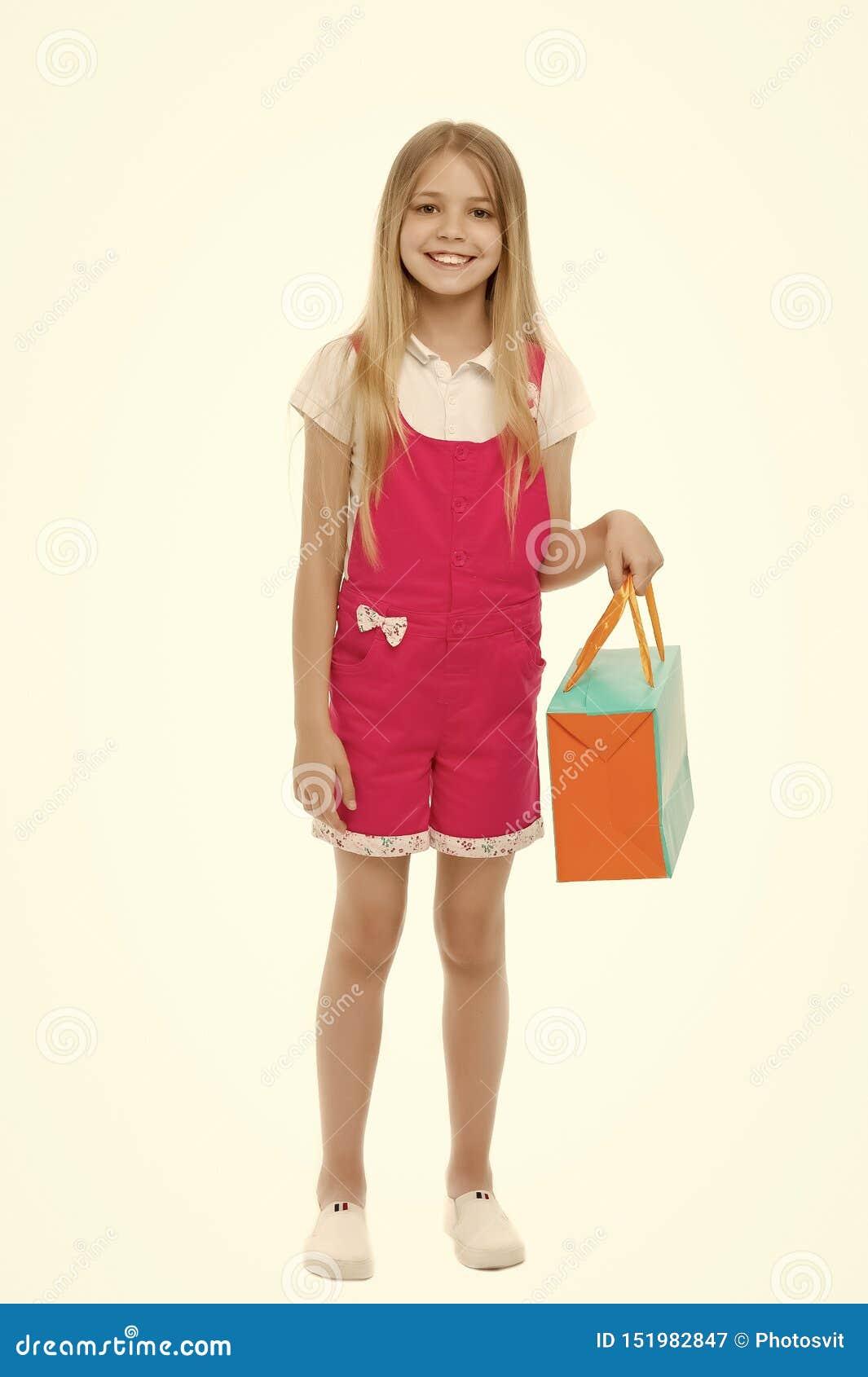 Fille heureuse avec le panier d isolement sur le blanc Sourire shopaholic de petite fille avec le sac de papier Client d enfant d