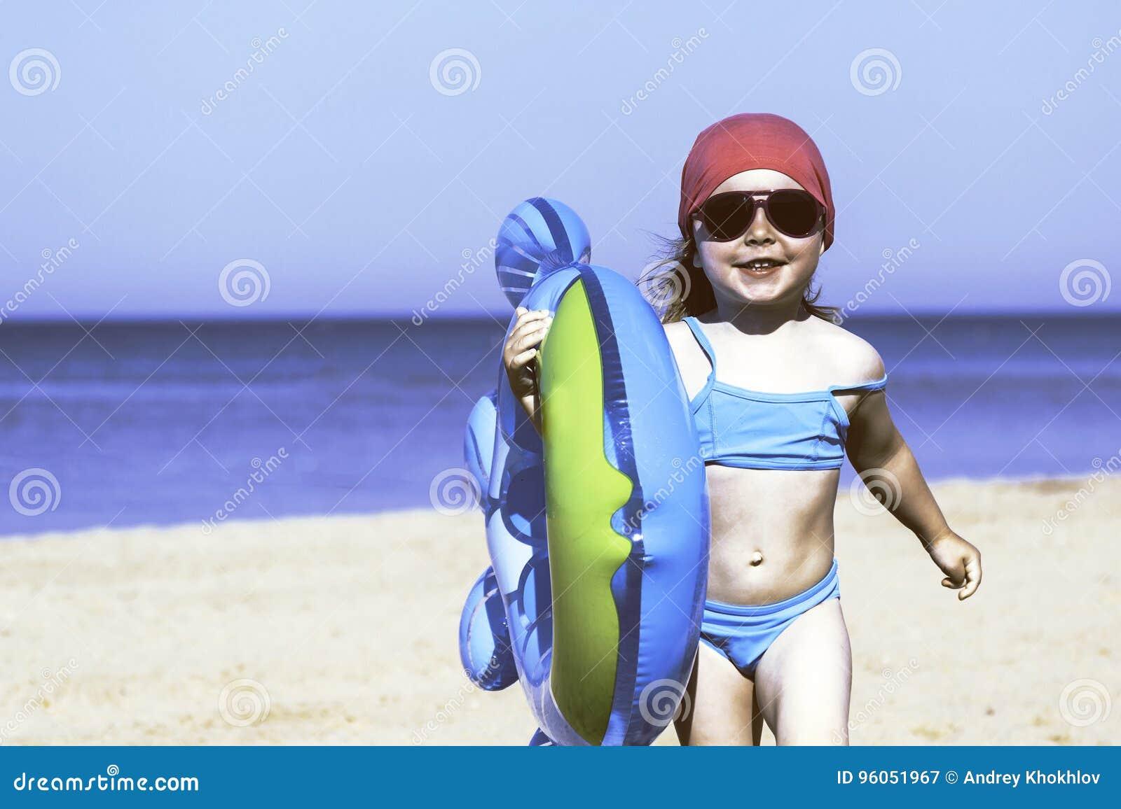 Fille heureuse avec un cercle gonflable sur la plage
