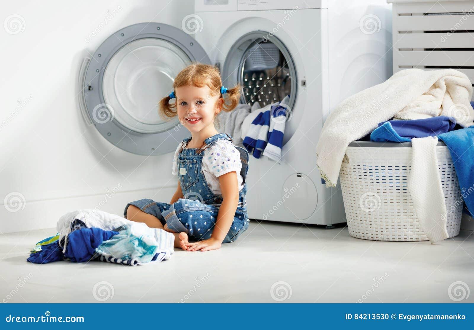 Fille heureuse d amusement d enfant petite pour laver des vêtements dans la buanderie