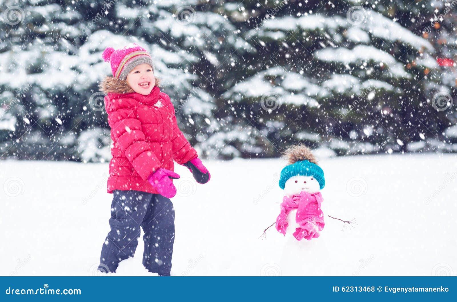 Fille heureuse d 39 enfant avec un bonhomme de neige sur une promenade d 39 hiver photo stock image - Bonhomme fille ...