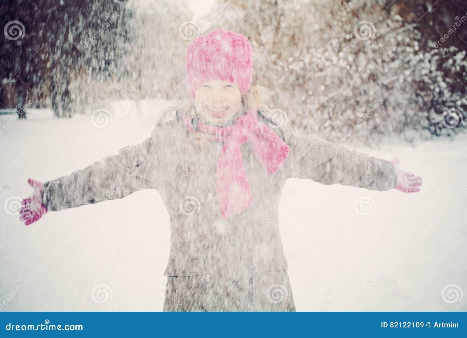 Fille heureuse d enfant ayant l amusement jouant avec la neige