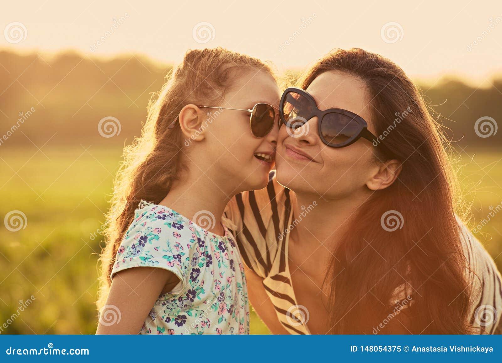 Fille heureuse d enfant de mode chuchotant sa m?re le secret dans des lunettes de soleil ? la mode dans la vue de profil et regar