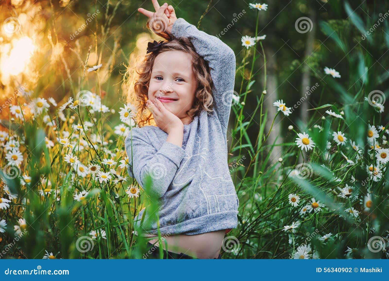Fille heureuse d enfant dupant sur le champ d été avec des fleurs
