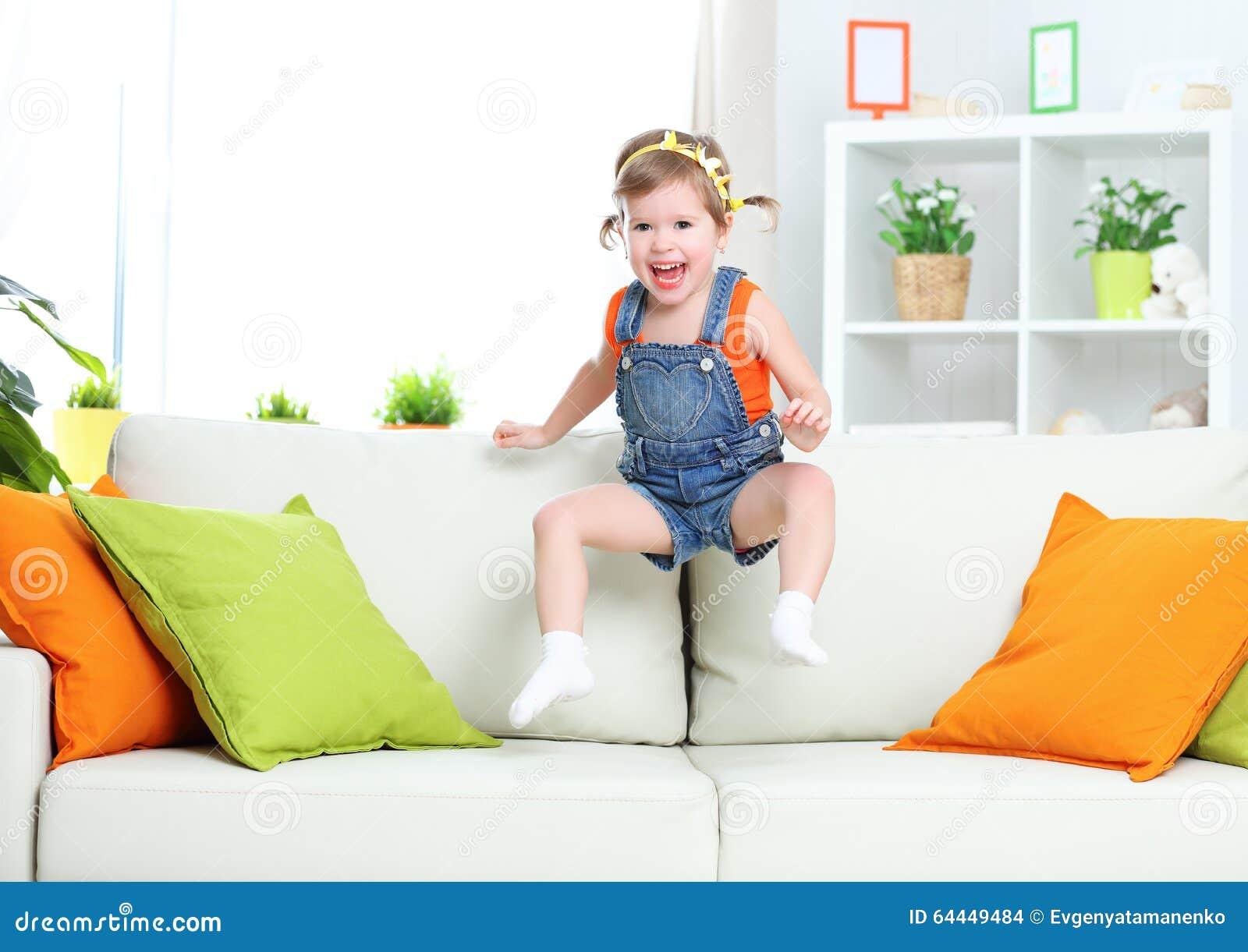 Fille heureuse d enfant jouant et sautant sur le divan à la maison