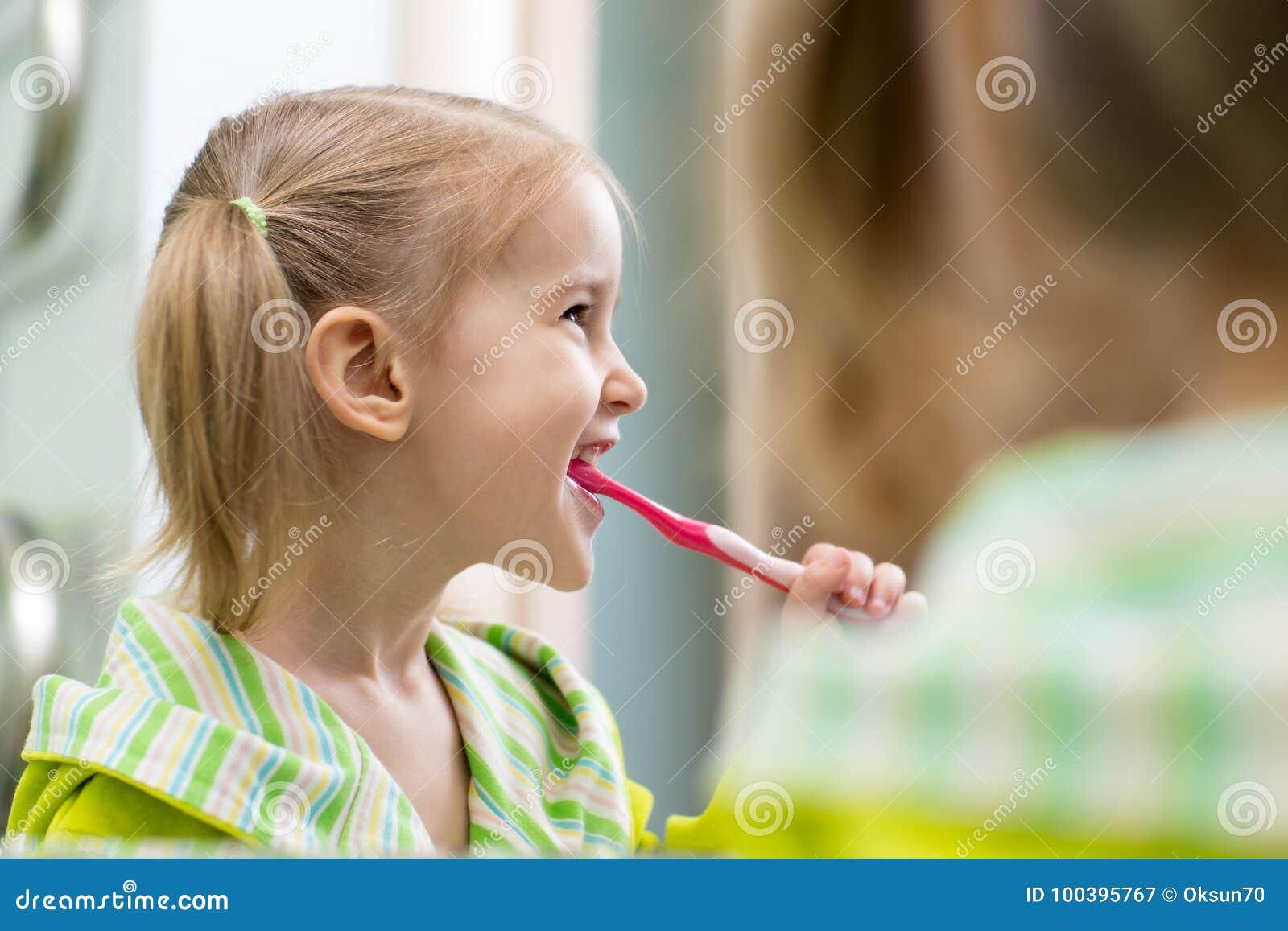 Fille heureuse d enfant regardant le miroir utilisant des dents de nettoyage de brosse à dents dans la salle de bains chaque mati