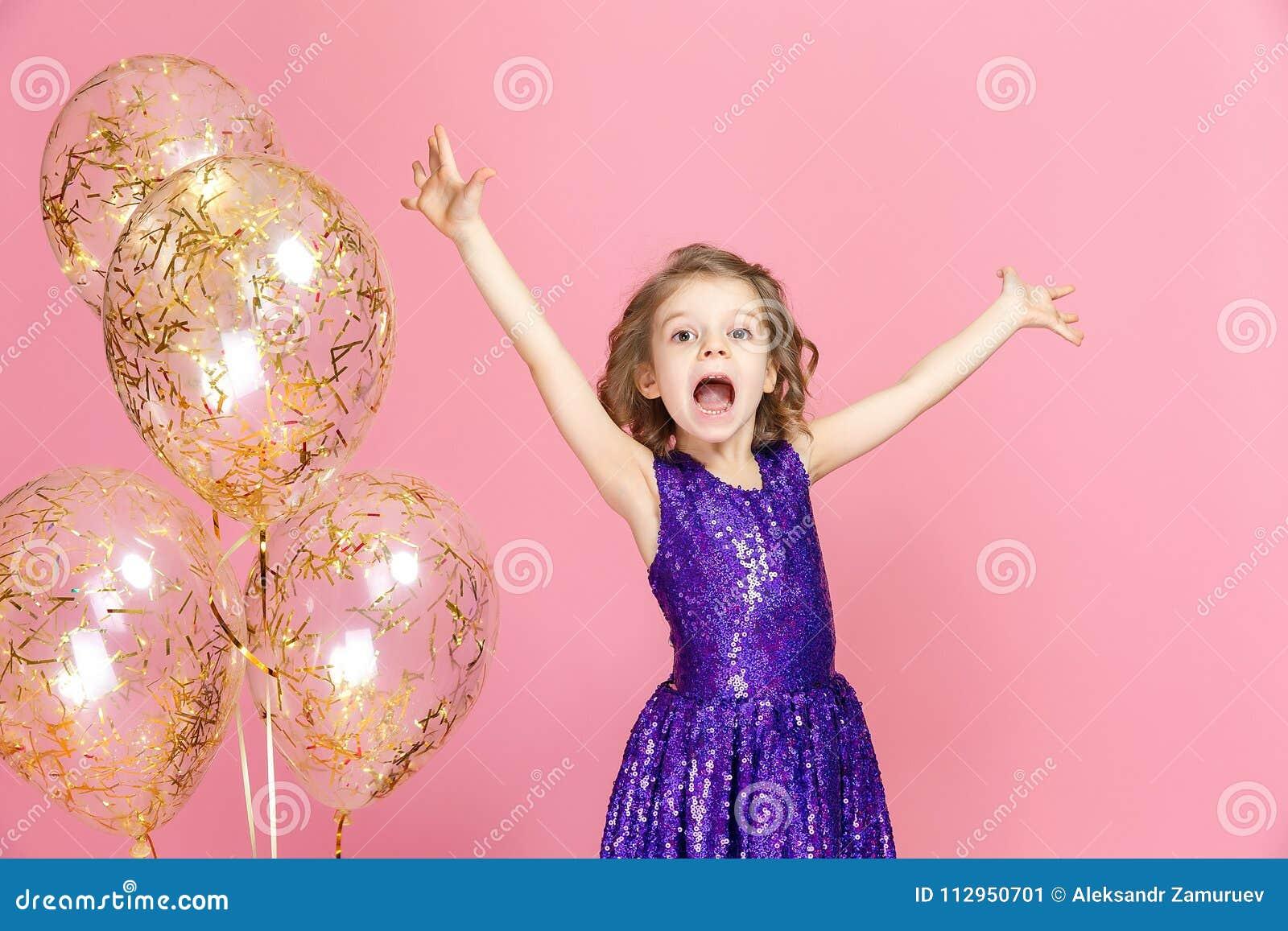 Fille heureuse dans la célébration rose de robe