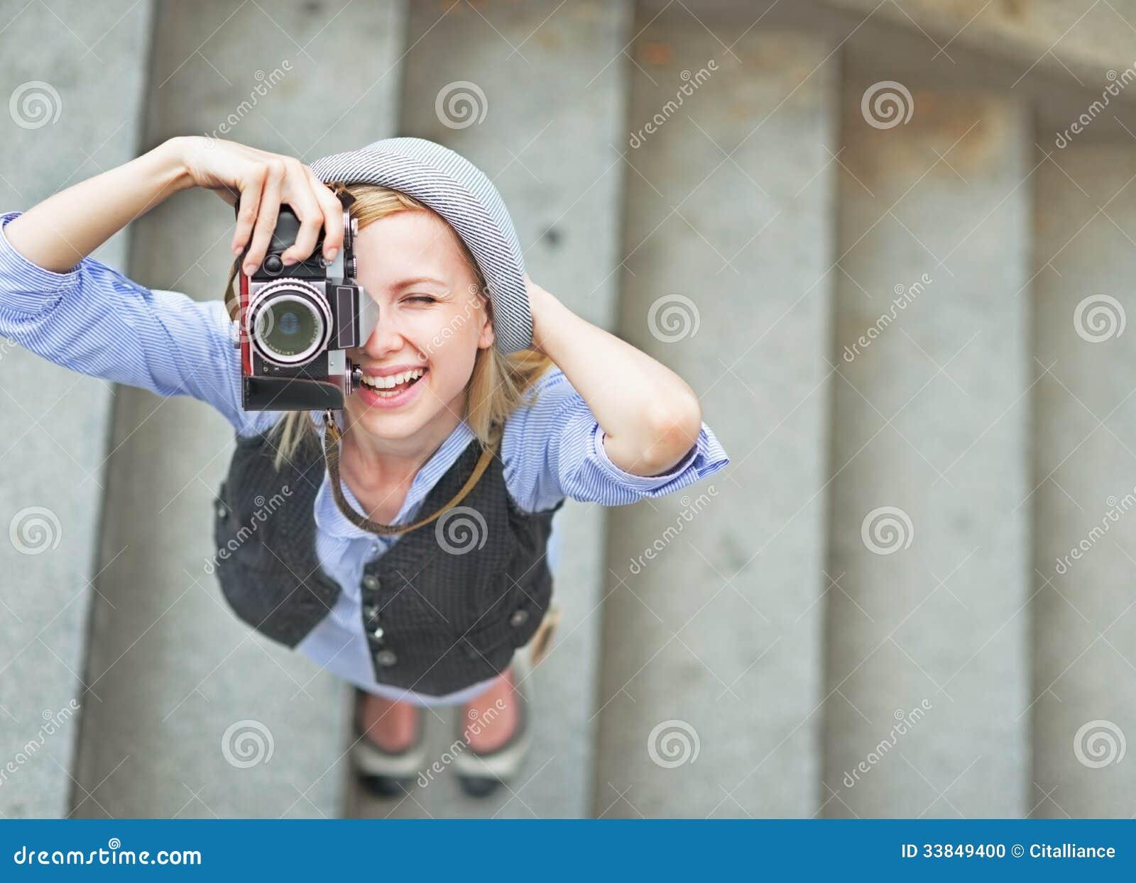 Fille heureuse de hippie faisant la photo avec le rétro appareil-photo sur la rue de ville