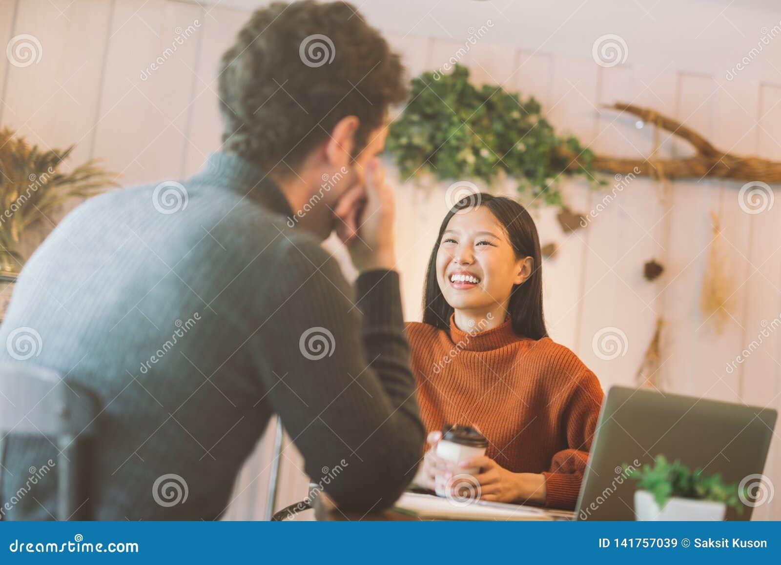 Fille heureuse et amis asiatiques causant et à l aide de l ordinateur portable en café au café de café à l université parlant et