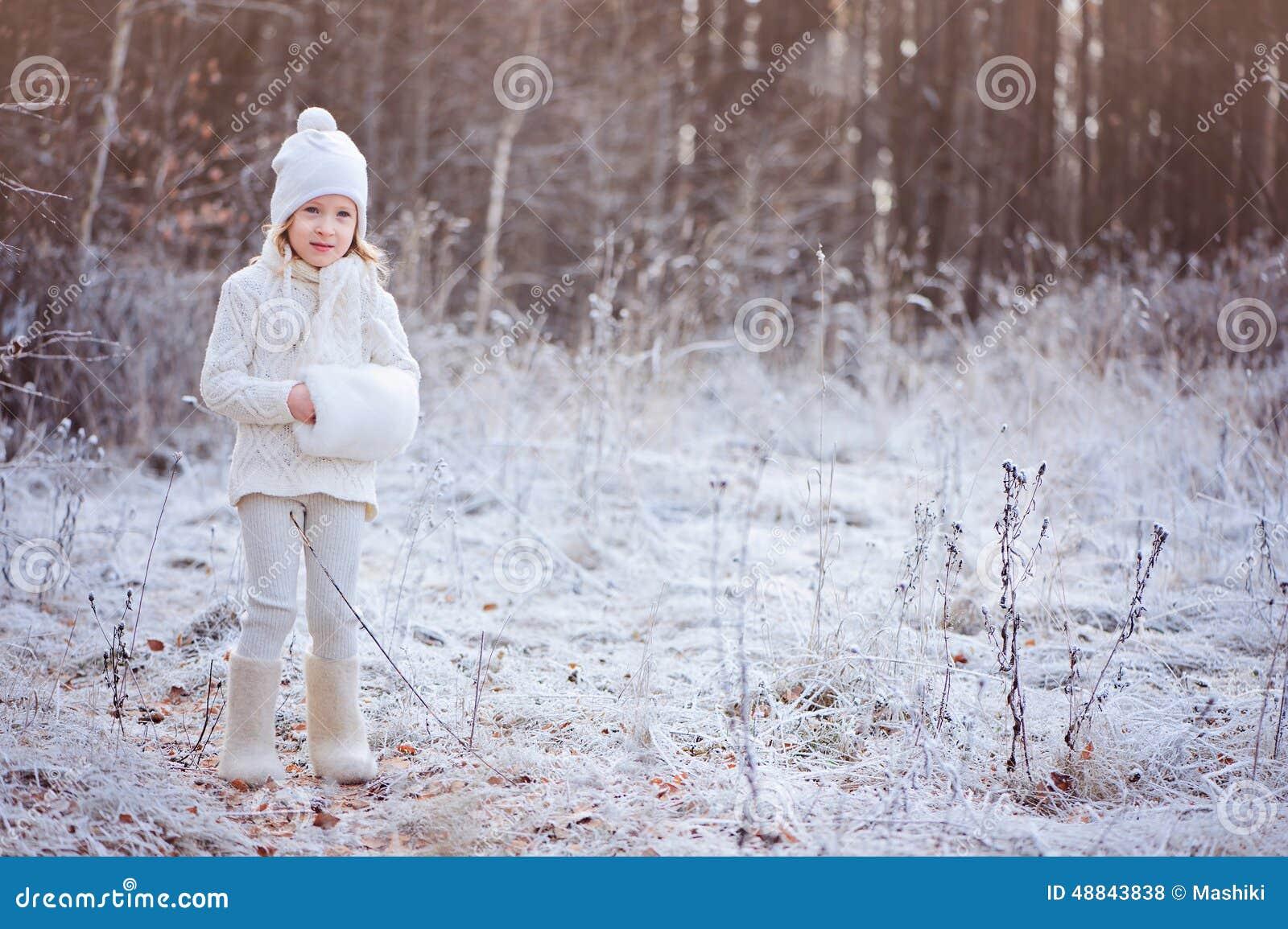 Fille heureuse mignonne d enfant dans l équipement blanc marchant dans la forêt congelée d hiver