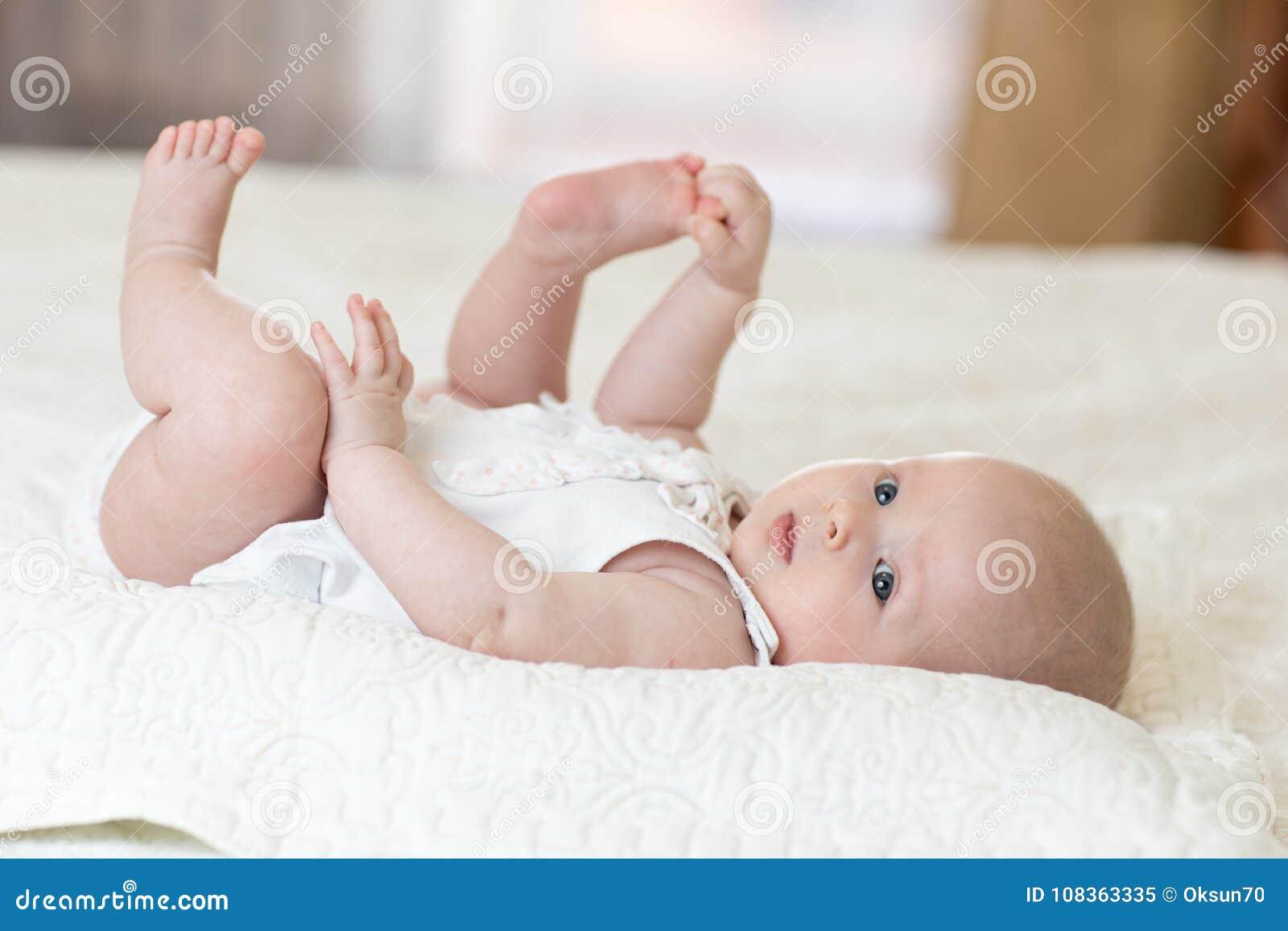 Fille infantile de bébé drôle jouant avec ses pieds
